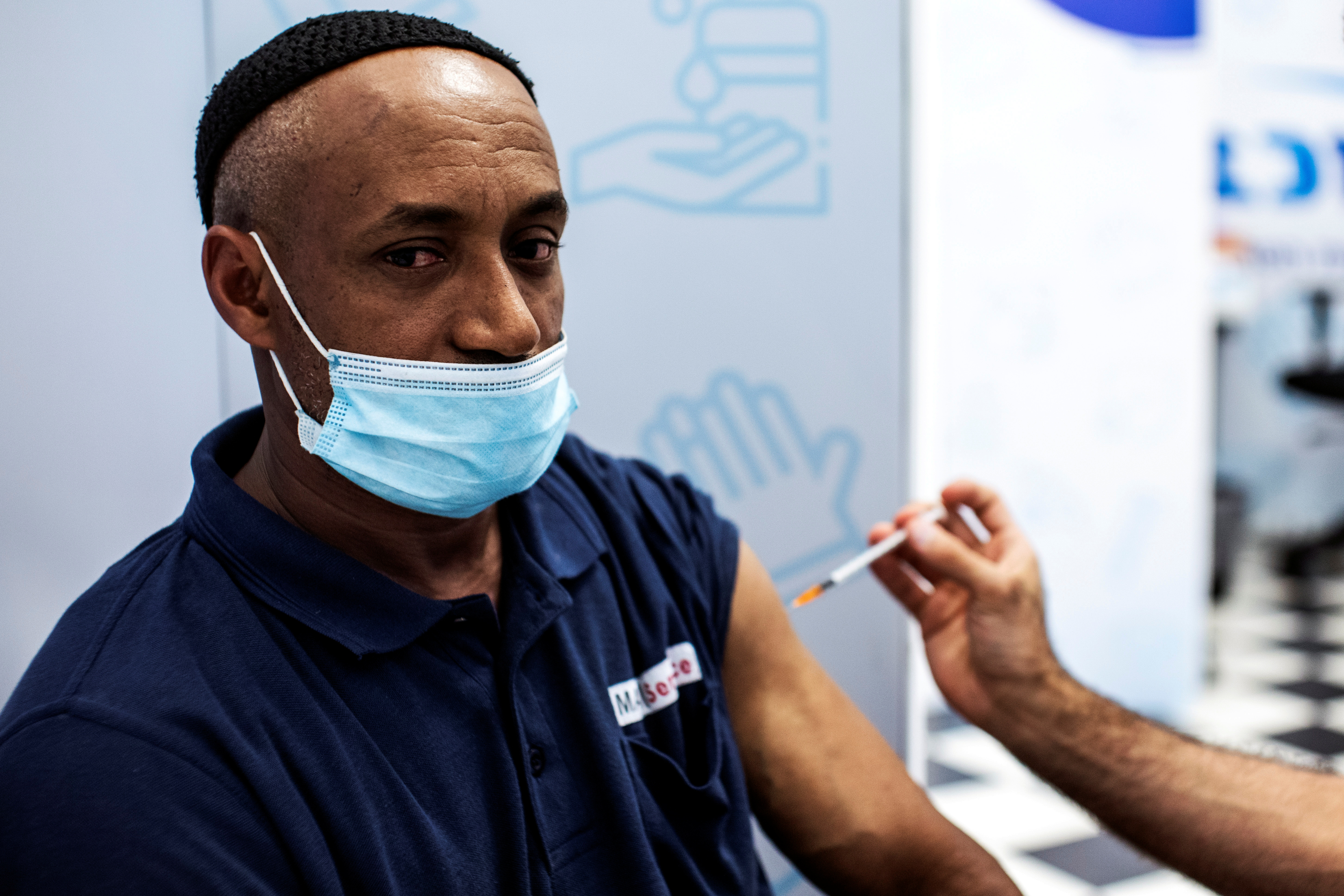 Israeli Izhak Mesfin, 44 years old, receives a third shot of coronavirus disease (COVID-19) vaccine as country launches booster shots for over 30-year-olds, in Rishon Lezion, Israel August 24, 2021. REUTERS/ Nir Elias
