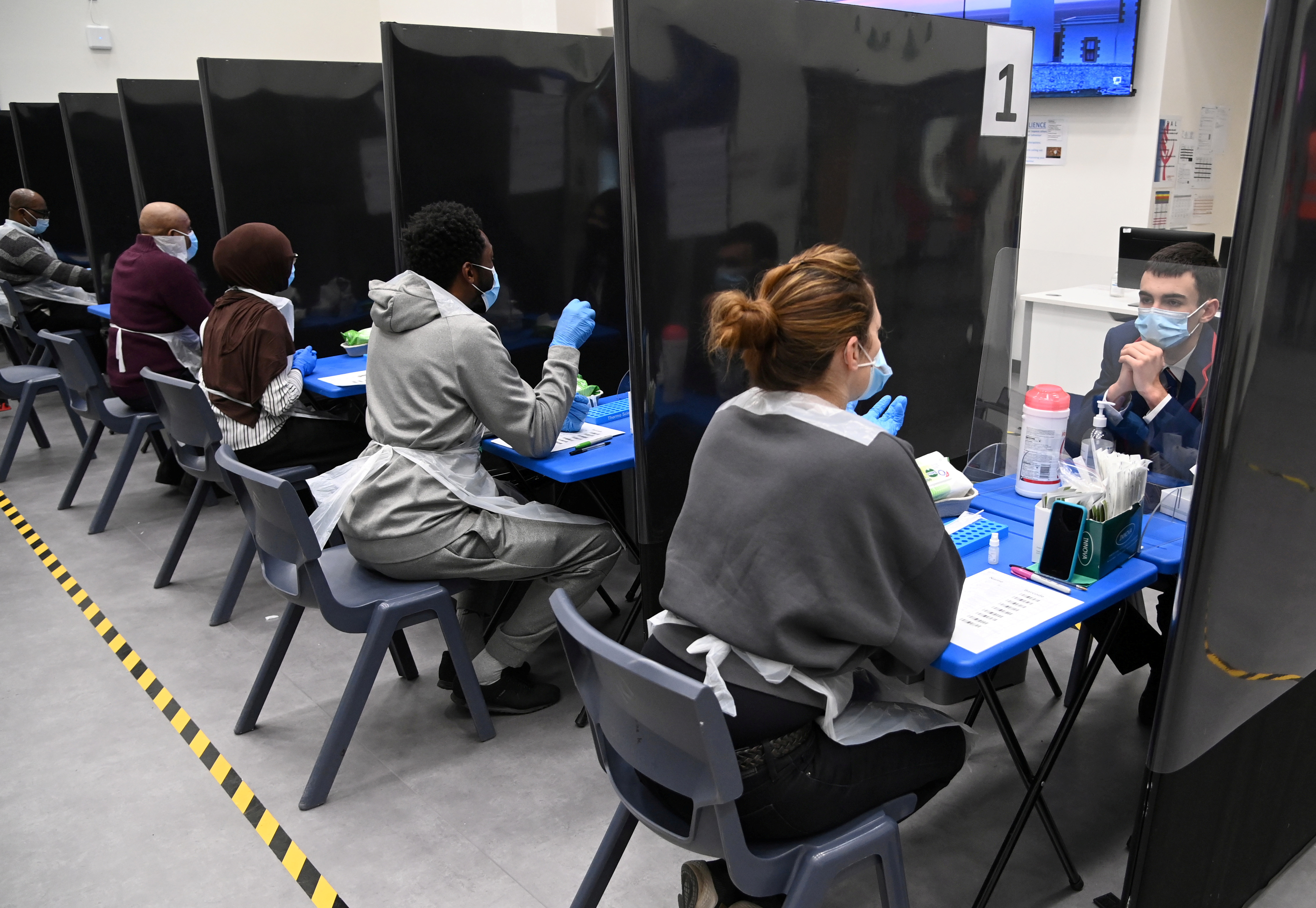 Health workers and volunteers assist as students take coronavirus disease (COVID-19) tests at Harris Academy Beckenham, ahead of full school reopening in England as part of lockdown restrictions being eased, in Beckenham, south east London, Britain, March 5, 2021. REUTERS/Toby Melville/