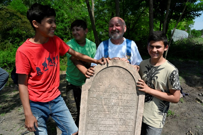 Local enthusiast Vladimir Spanik, 73, and boys from the Roma community work to restore a forgotten Jewish cemetery in the village of Vinodol, Slovakia June 5, 2021. Picture taken June 5, 2021. REUTERS/Radovan Stoklasa