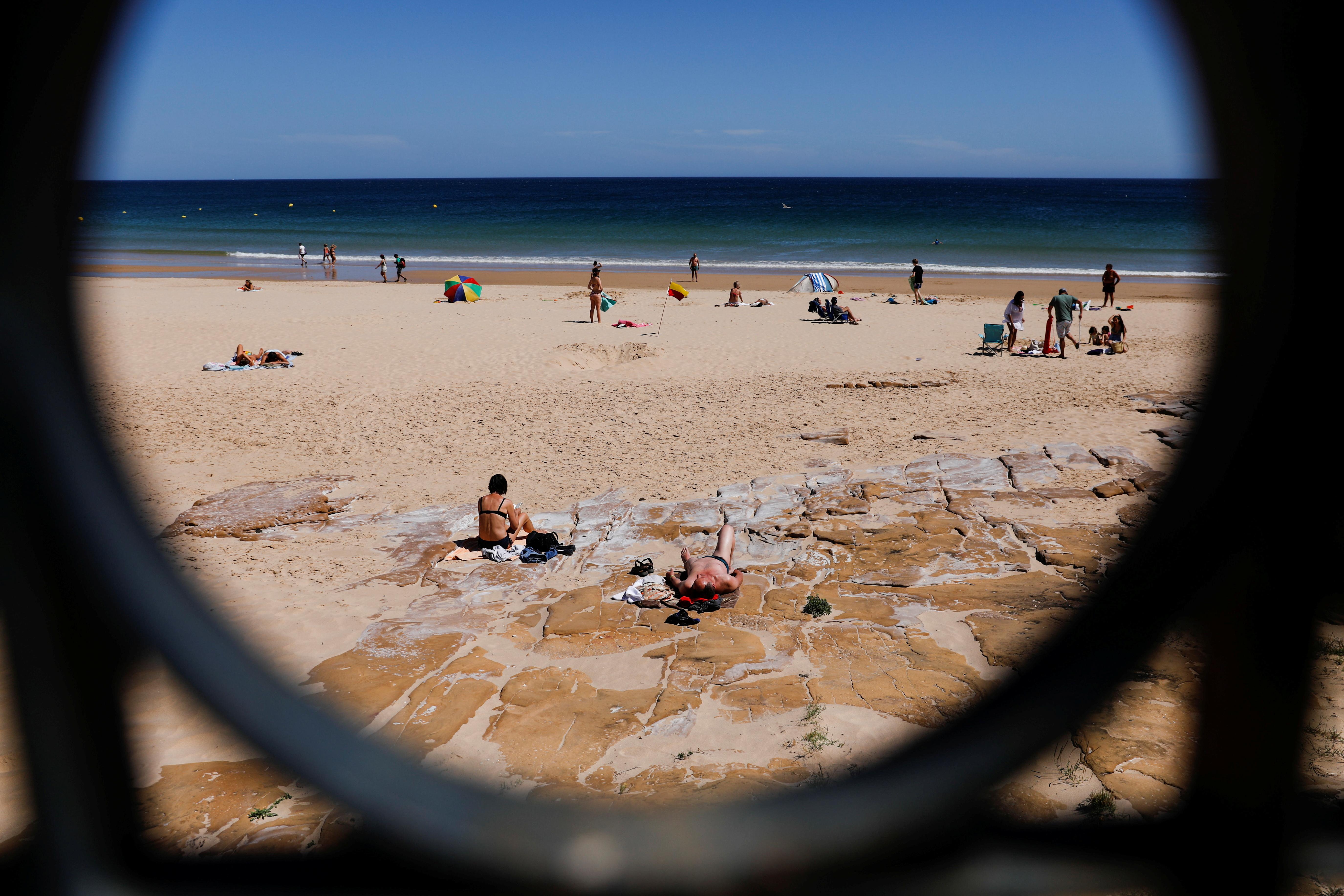 ผู้คนอาบแดดบนชายหาด Luz ท่ามกลางการแพร่ระบาดของโรค coronavirus (COVID-19) ในลากอสประเทศโปรตุเกส 3 มิถุนายน 2021 REUTERS / Pepro Nunes