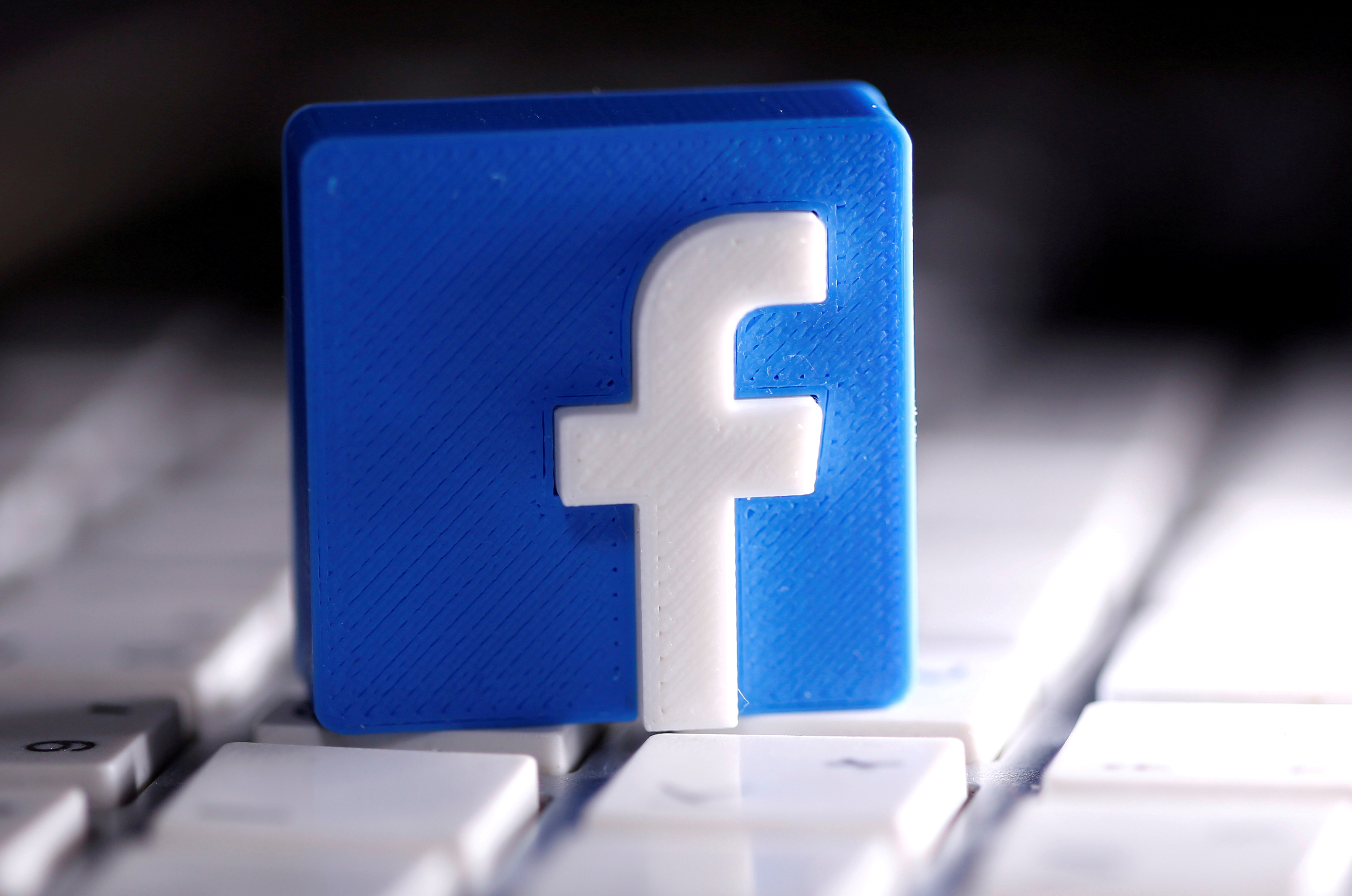 A 3D-printed Facebook logo is seen placed on a keyboard, March 25, 2020. REUTERS/Dado Ruvic