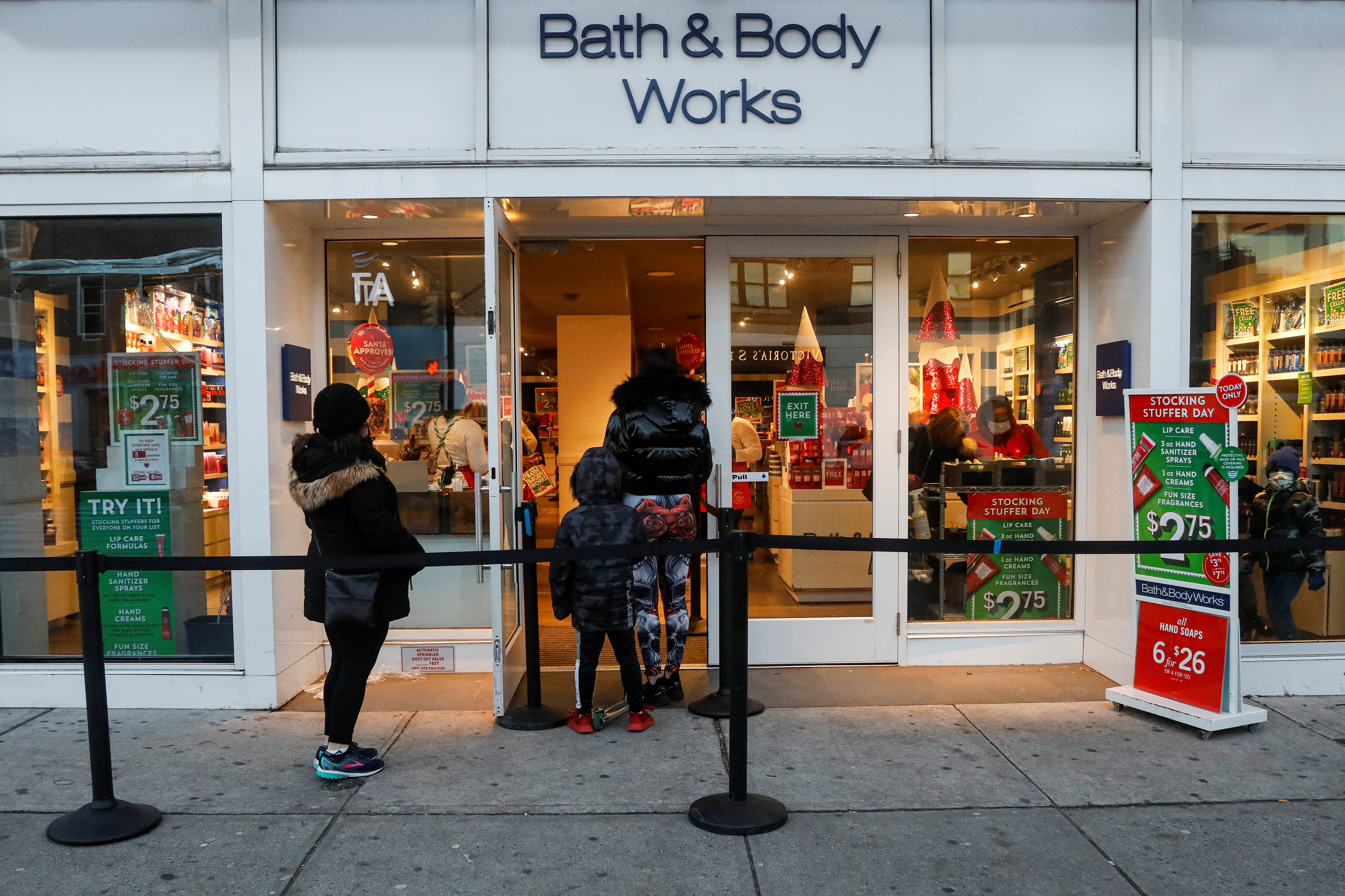 Shoppers wait in line outside a Bath and Body Works retail store, as the global outbreak of the coronavirus disease (COVID-19) continues,  in Brooklyn, New York, U.S., December 8, 2020.  REUTERS/Brendan McDermid