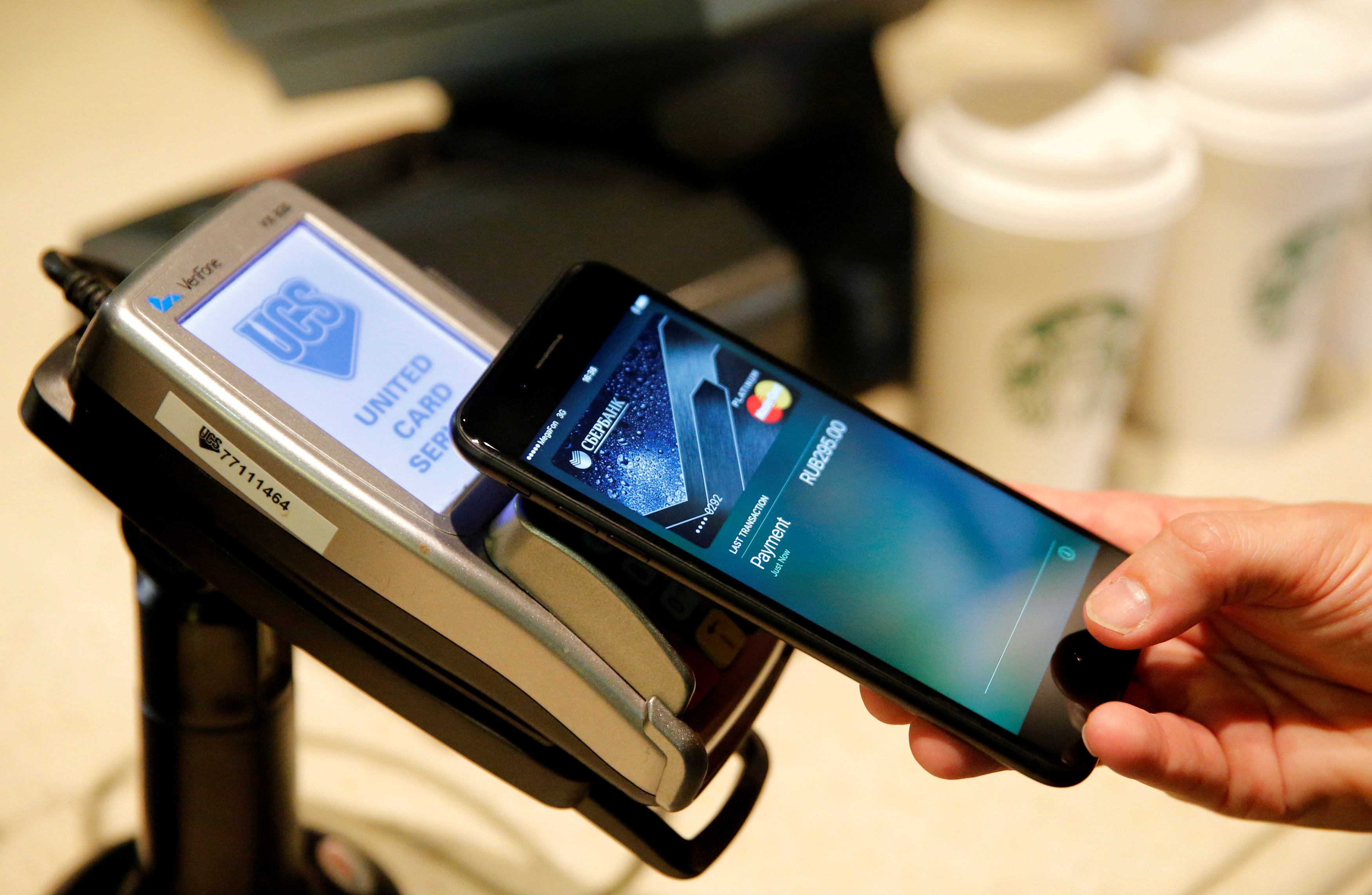 A man uses an iPhone 7 smartphone to demonstrate the mobile payment service Apple Pay at a cafe in Moscow, Russia, October 3, 2016. Picture taken October 3, 2016.   REUTERS/Maxim Zmeyev/File Photo