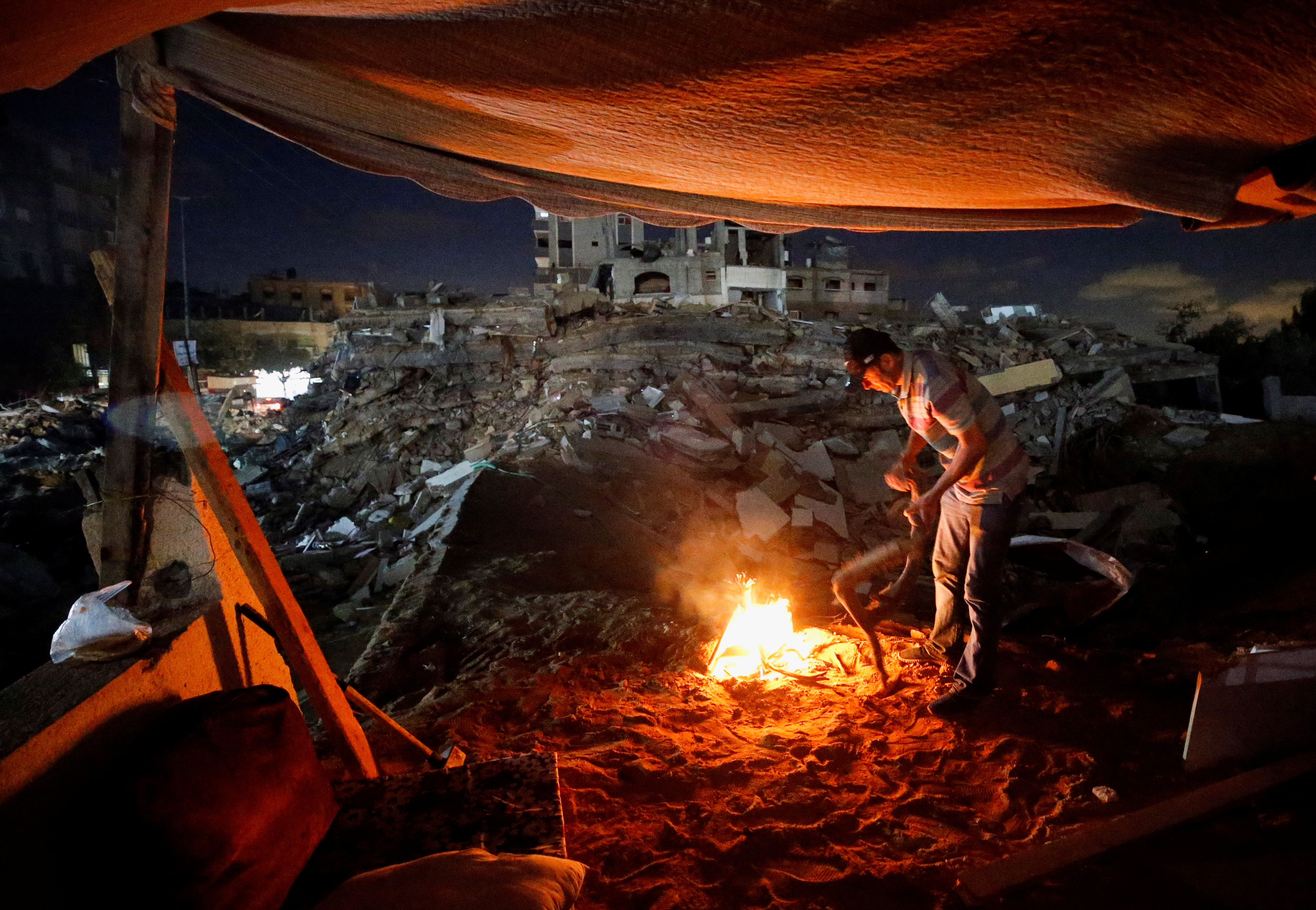 A Palestinian man lights a fire amid the rubble of his house which was destroyed by Israeli air strikes during the Israel-Hamas fighting, in Gaza Strip, May 23, 2021. REUTERS/Ahmed Jadallah.