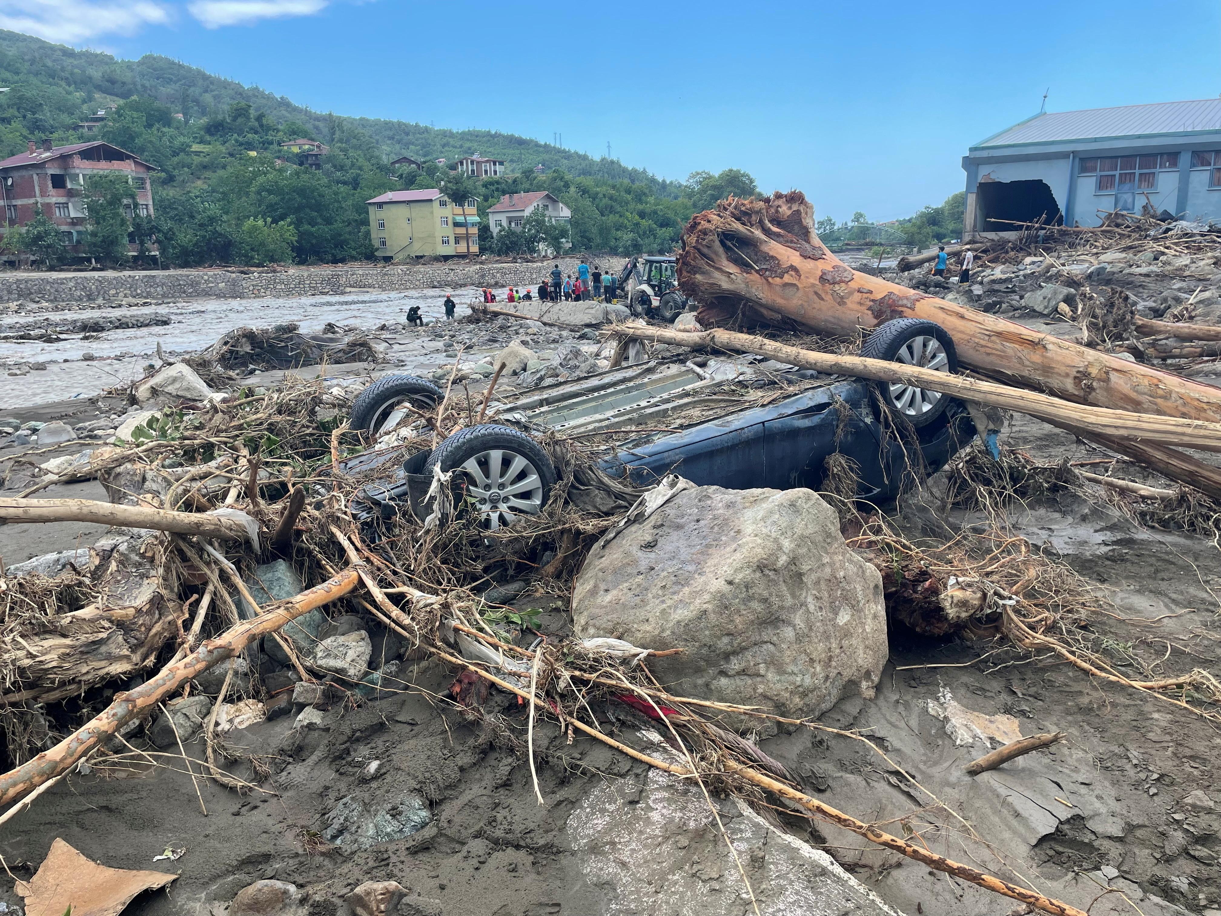 The wreckage of a vehicle is seen amid debris after flash floods swept through towns in the Turkish Black Sea region, in the town of Bozkurt, in Kastamonu province, Turkey, August 14, 2021. REUTERS/Mehmet Emin Caliskan