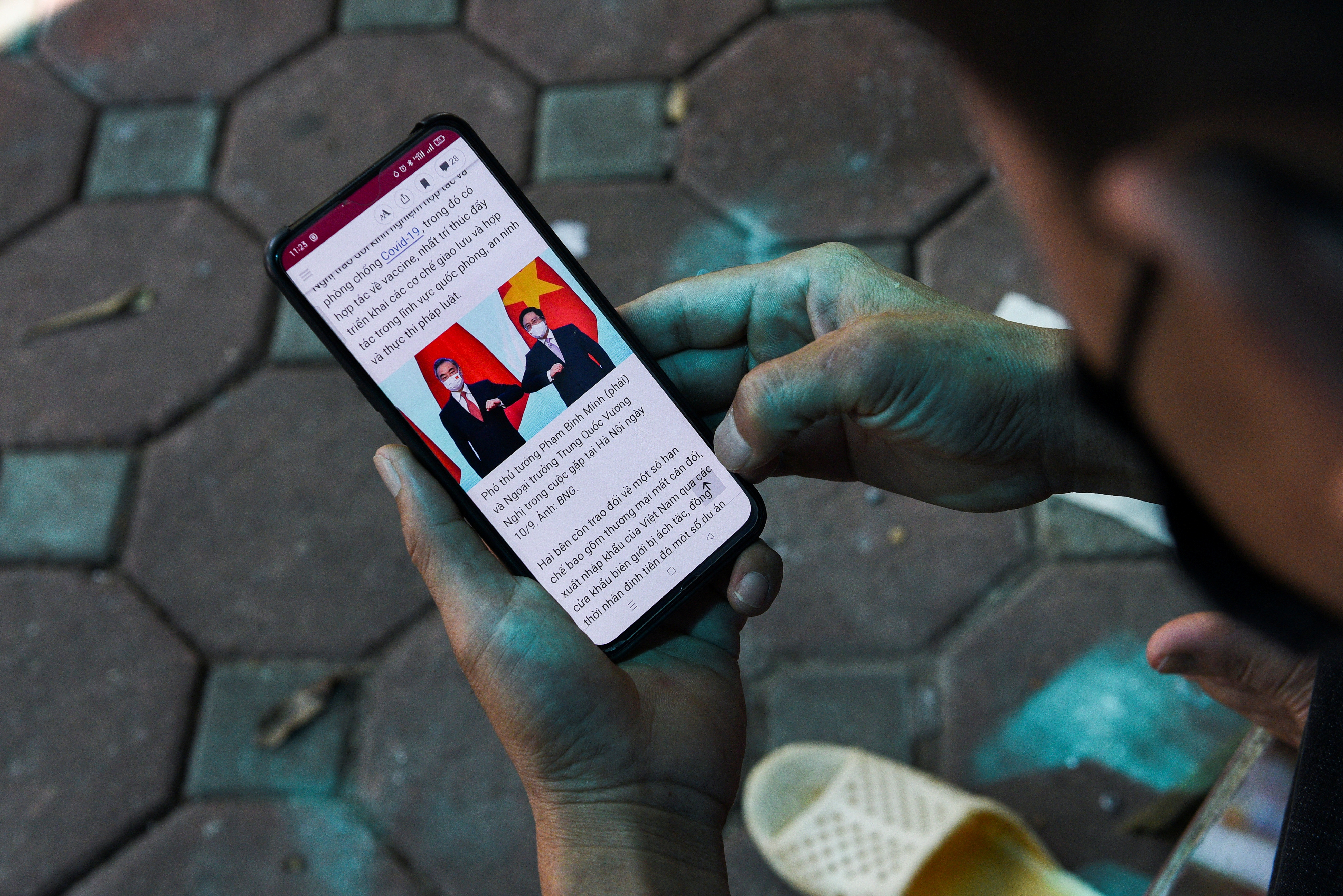 A man reads the news about Chinese foreign minister Wang Yi's visit to Vietnam, at a street in Hanoi, Vietnam, September 11, 2021. REUTERS/Stringer
