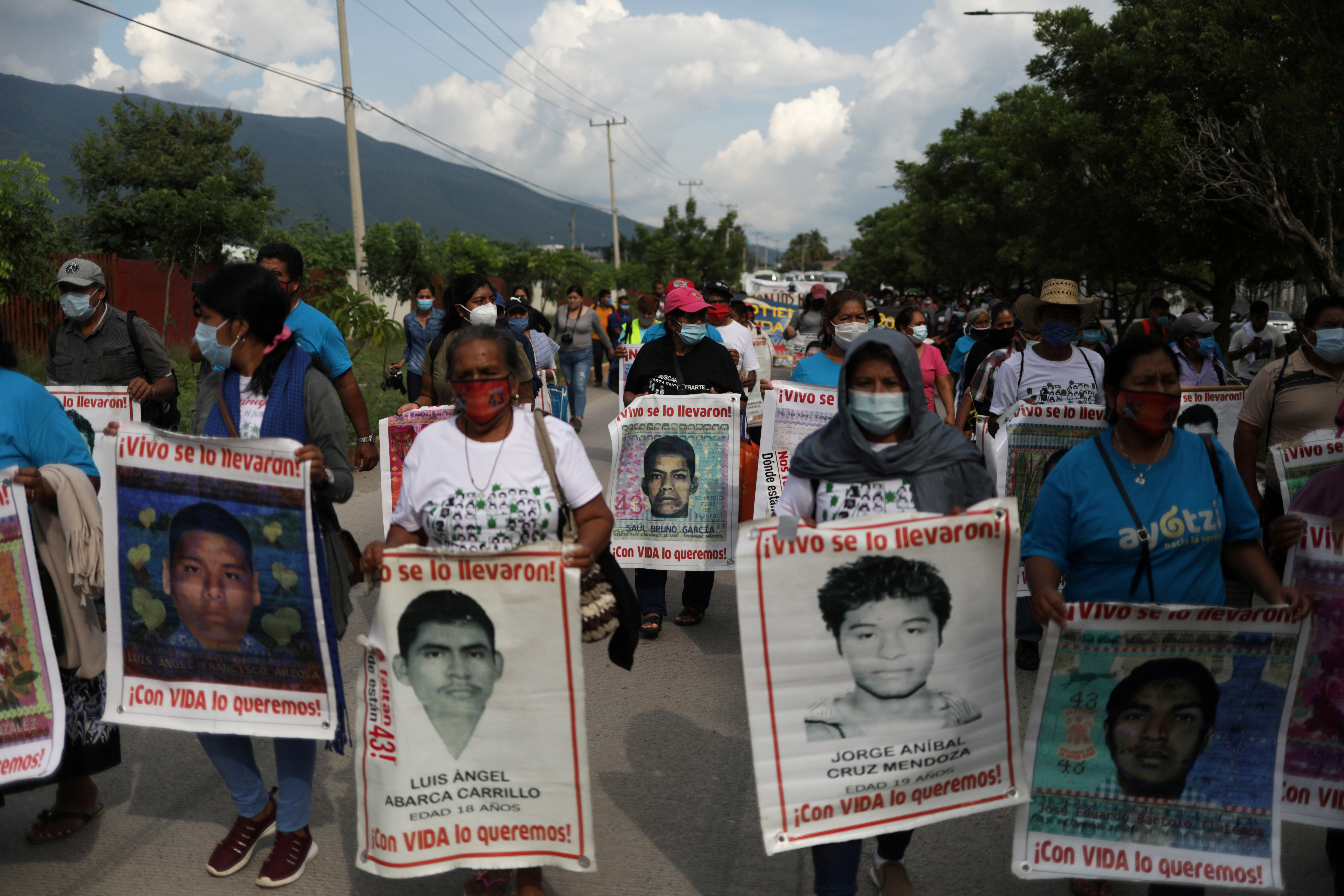 Relatives of missing students hold posters with their images as they take part in a march to mark the sixth anniversary of the disappearance of 43 students of the Ayotzinapa Teacher Training College, in Iguala in the southwestern state of Guerrero, Mexico September 27, 2020. REUTERS/Henry Romero