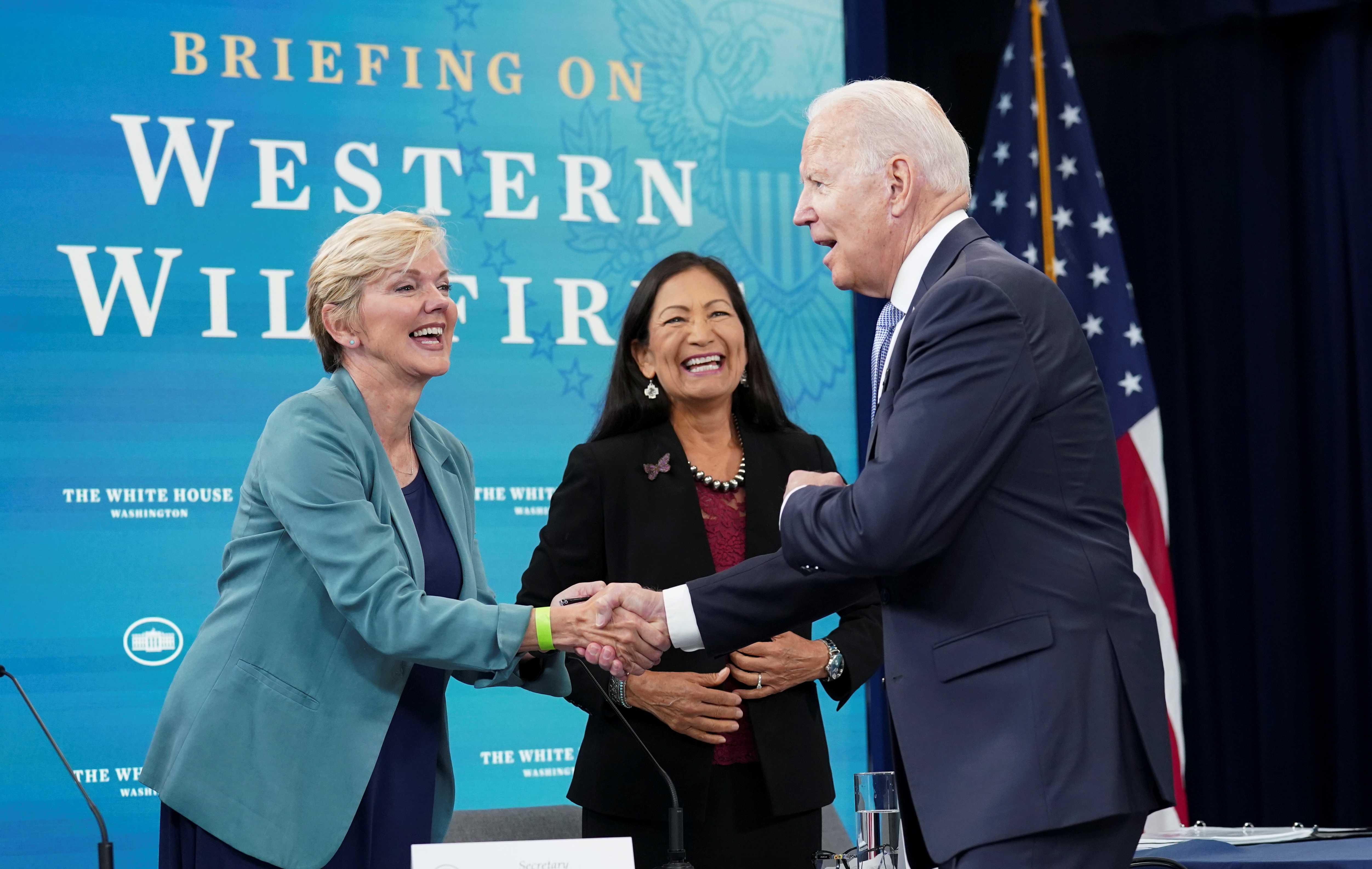 U.S. President Joe Biden shakes hands with Energy Secretary Jennifer Granholm next to Interior Secretary Deb Haaland as he arrives for a meeting with cabinet officials, governors, and private sector partners to discuss preparedness of Western states to heat, drought and wildfires this season, at the White House in Washington, U.S. June 30, 2021. REUTERS/Kevin Lamarque