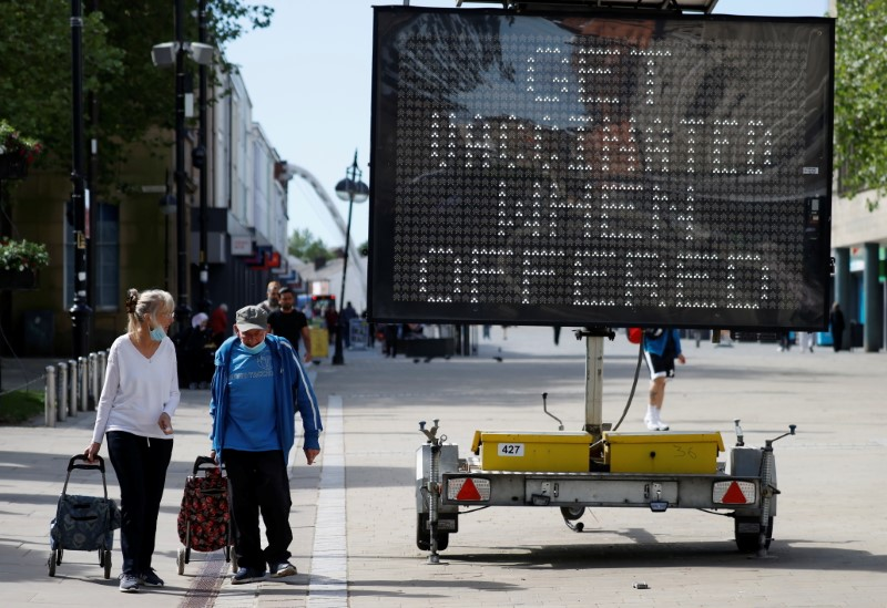 People pull shopping carts as they walk past an information board, amid the outbreak of the coronavirus disease (COVID-19), in Bolton, Britain, June 16, 2021. REUTERS/Phil Noble