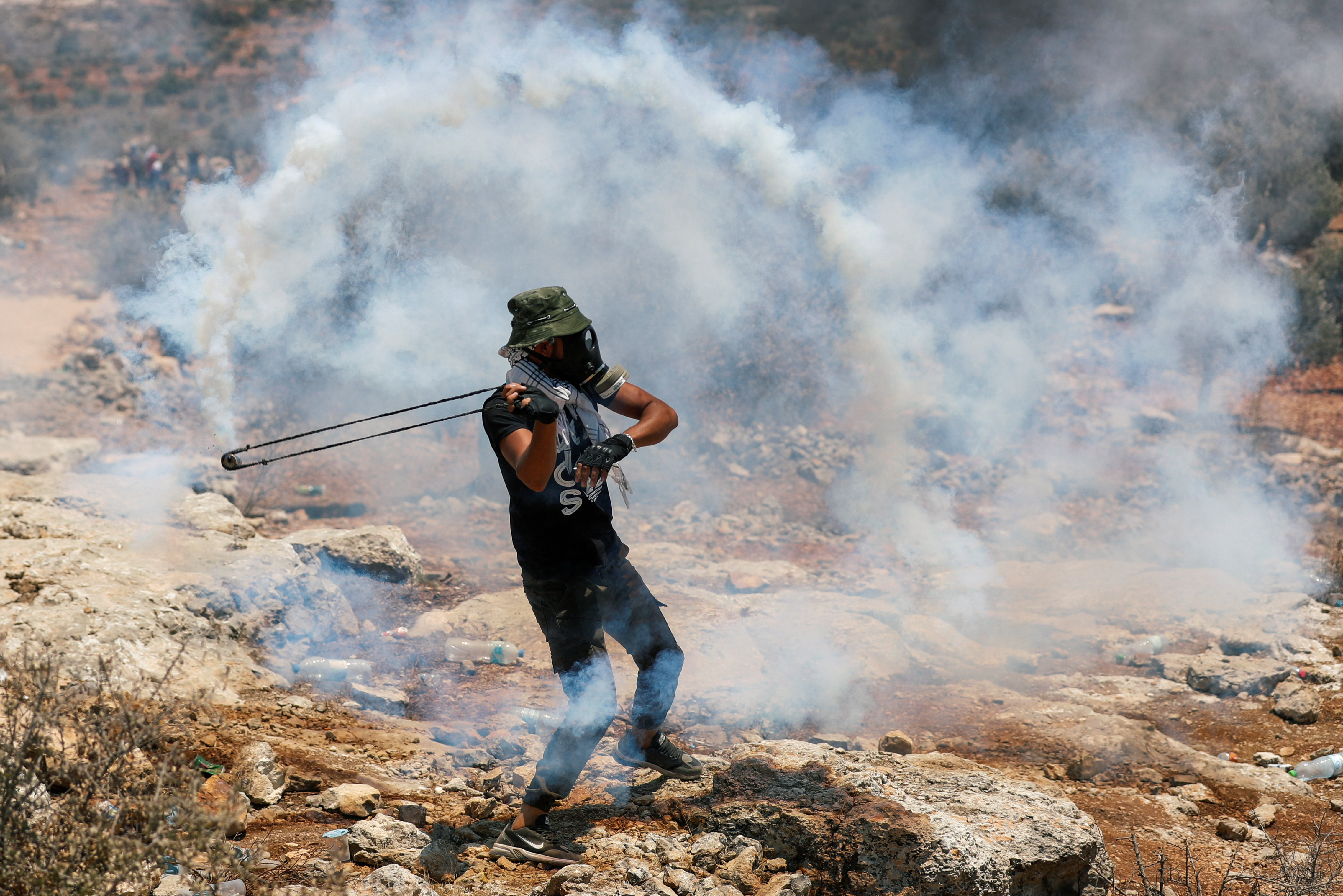 A Palestinian demonstrator uses a slingshot during a protest against Israeli settlements, in Beita, in the Israeli-occupied West Bank July 9, 2021. REUTERS/Mohamad Torokman