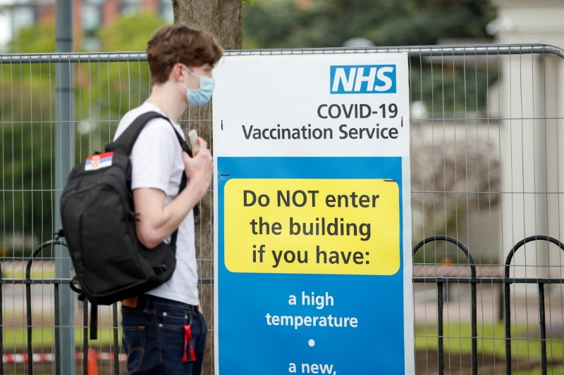 A person waits to receive the coronavirus disease (COVID-19) vaccine next to an information board, in Leicester, Britain May 27, 2021. REUTERS/Andrew Boyers