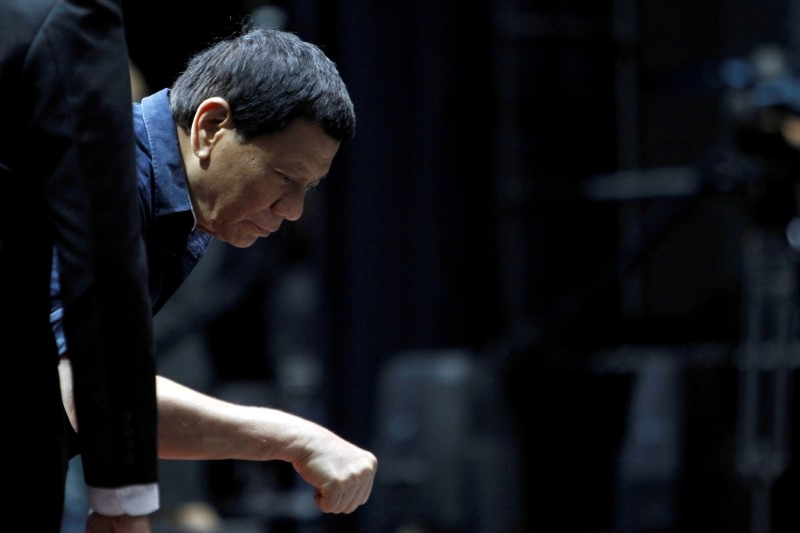 Philippines President Rodrigo Duterte fist bumps a supporter at a community gathering event in Singapore, April 28, 2018. REUTERS/Feline Lim/File Photo