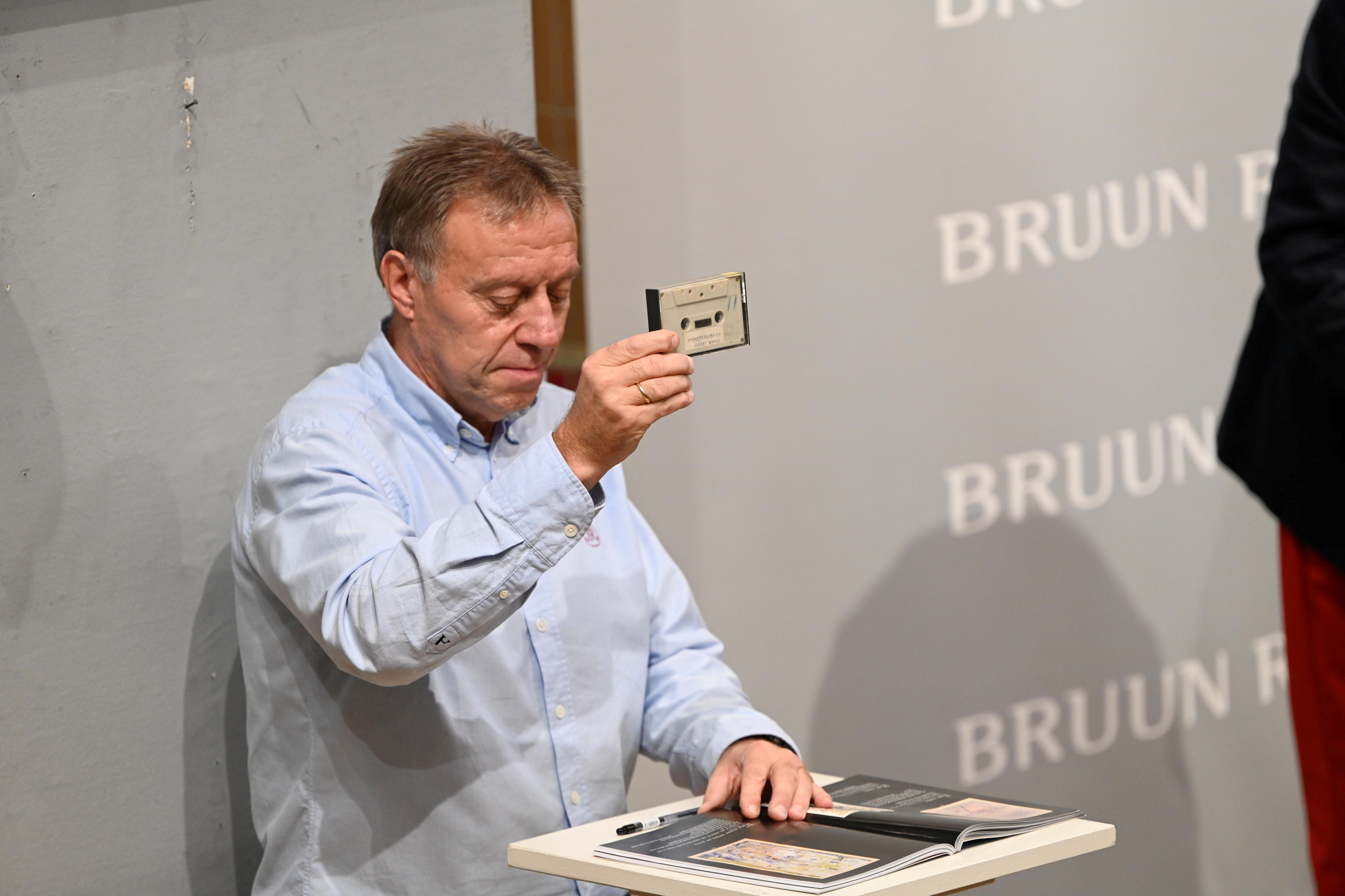 A staff member displays the cassette with the recording of four Danish schoolboys' interviews with John Lennon and Yoko Ono during the couple's winter stay in Thy, Jutland, Denmark in 1970 at Bruun Rasmussen Auction House in Copenhagen, Denmark, September 28, 2021. The auction includes the interviews and song