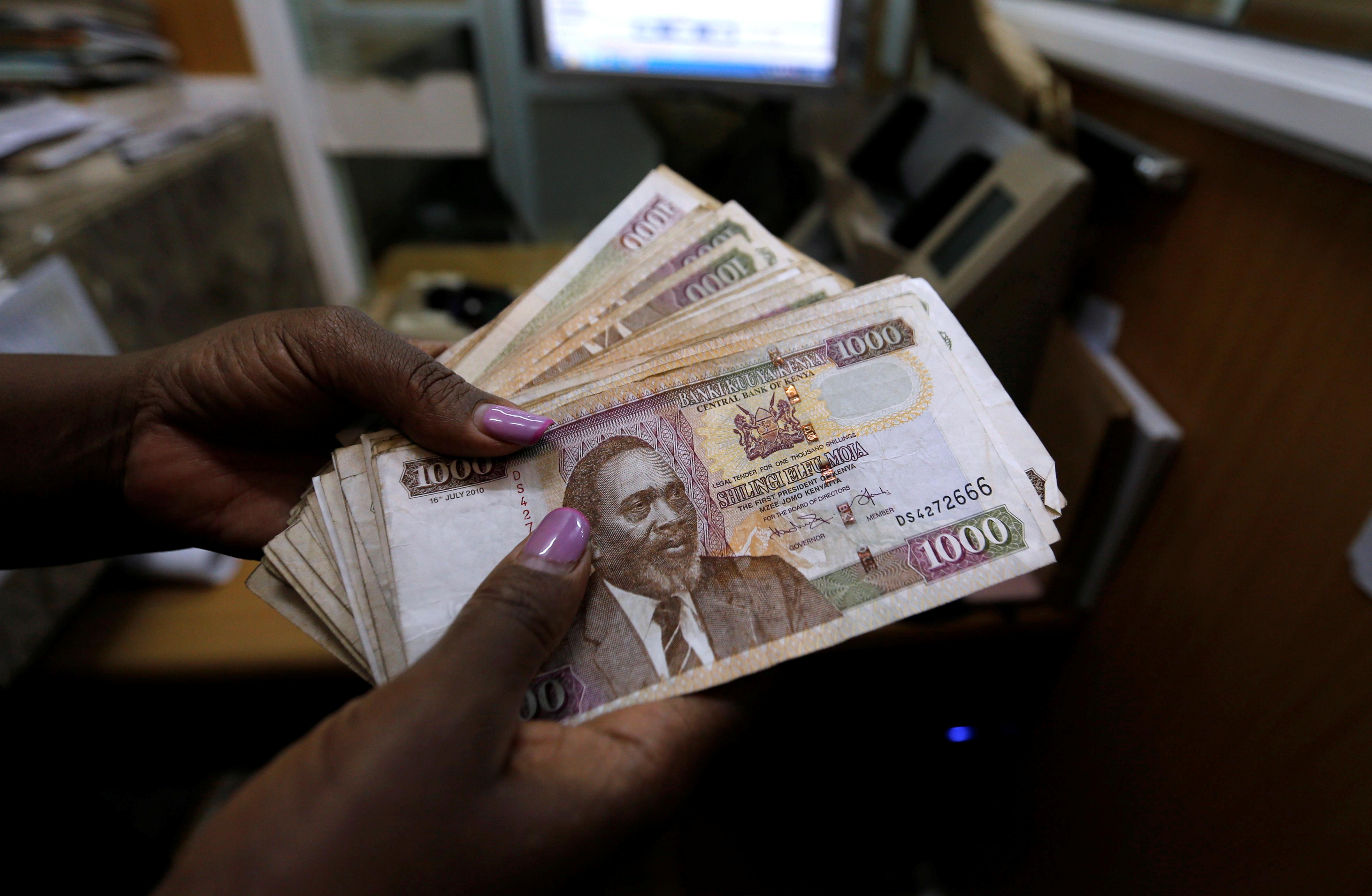 A teller counts Kenya shilling notes inside the cashier's booth at a forex exchange bureau in Kenya's capital Nairobi, April 20, 2016. REUTERS/Thomas Mukoya