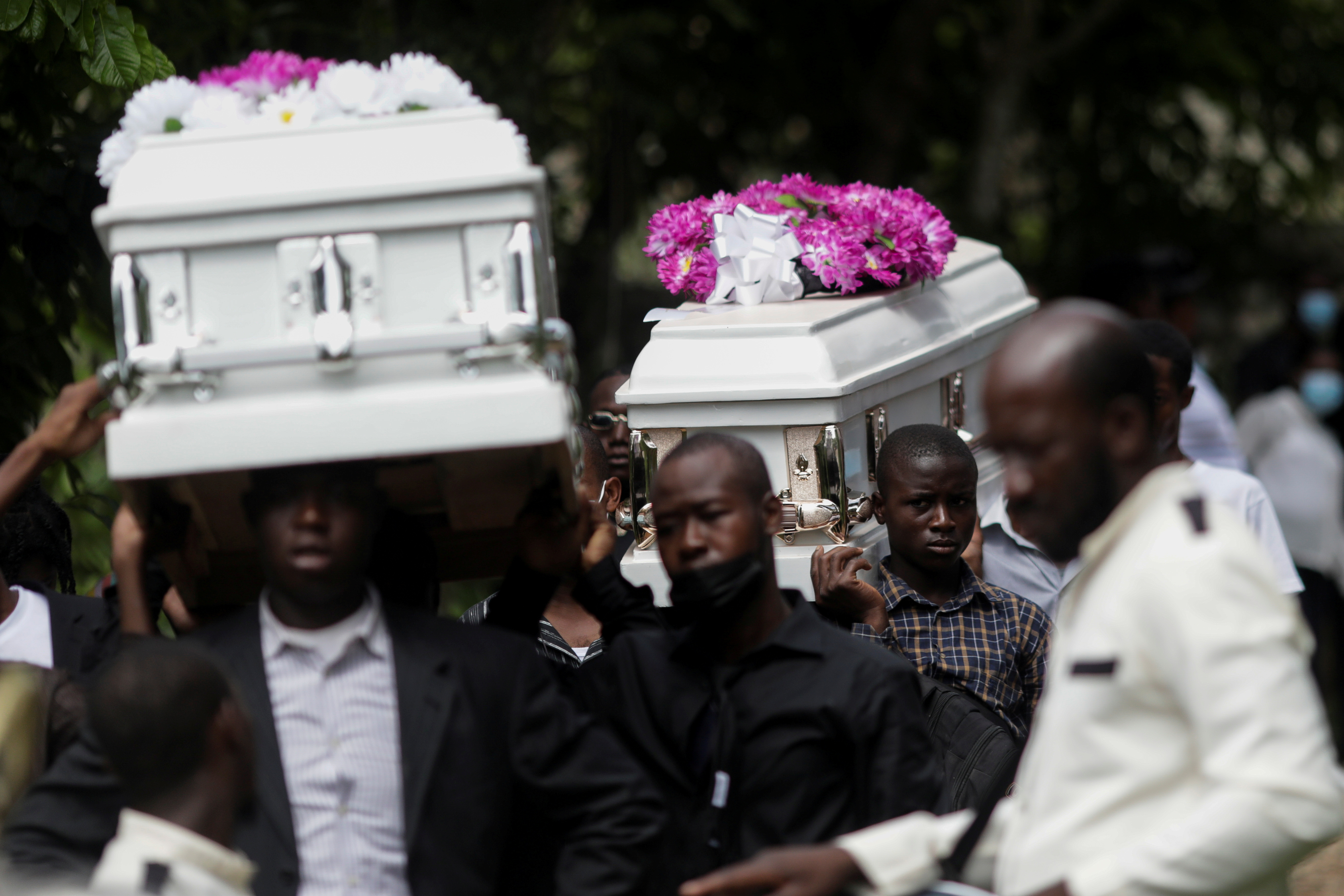 People carry coffins during the funeral of four family members after the earthquake that took place on August 14th, in Marceline near Les Cayes, Haiti August 21, 2021. REUTERS/Henry Romero