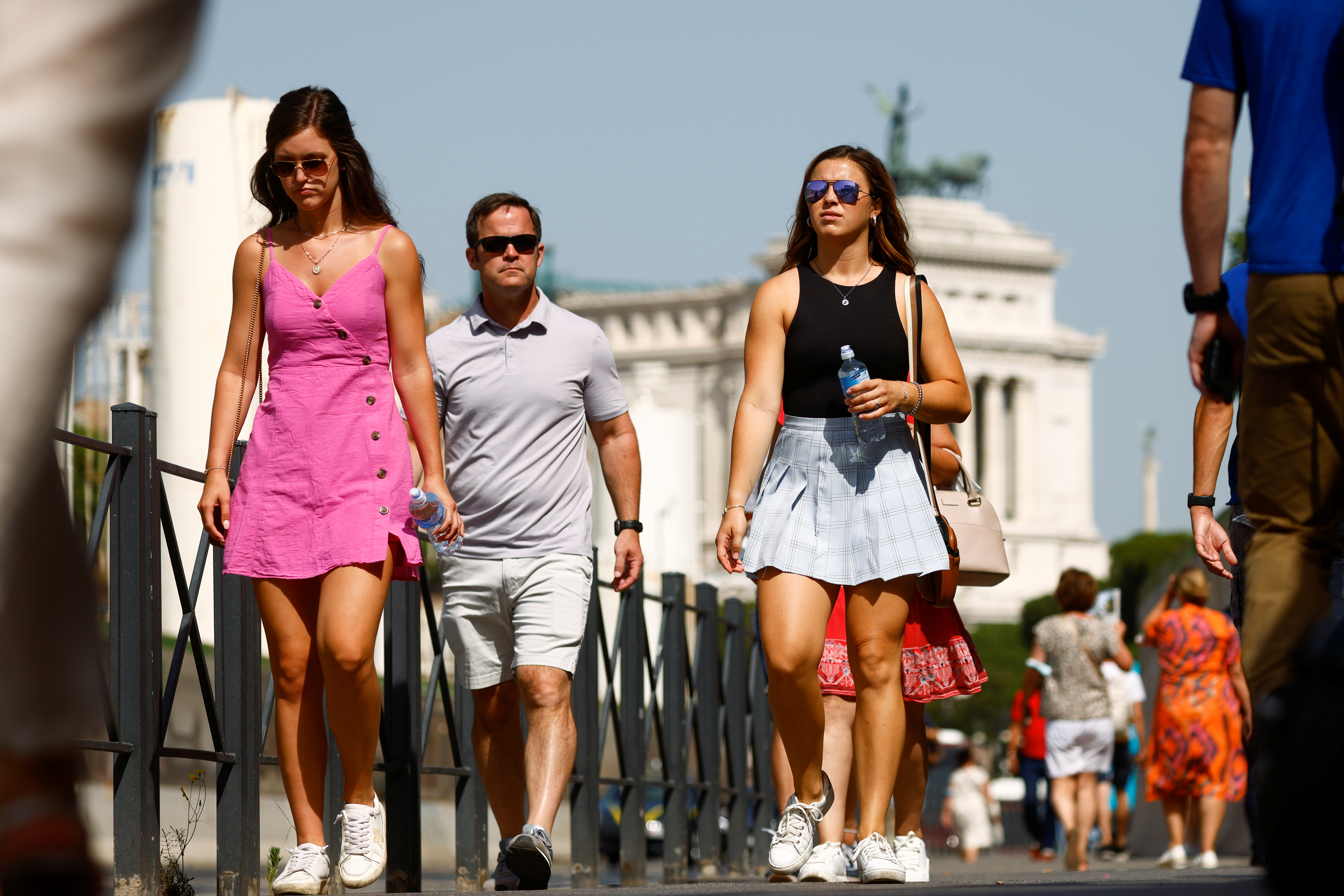 People walk without wearing masks as Italy lifts mandatory masks outdoors thanks to a decline in the coronavirus disease (COVID-19) cases and hospitalisations, in Rome, Italy, June 28, 2021. REUTERS/Guglielmo Mangiapane