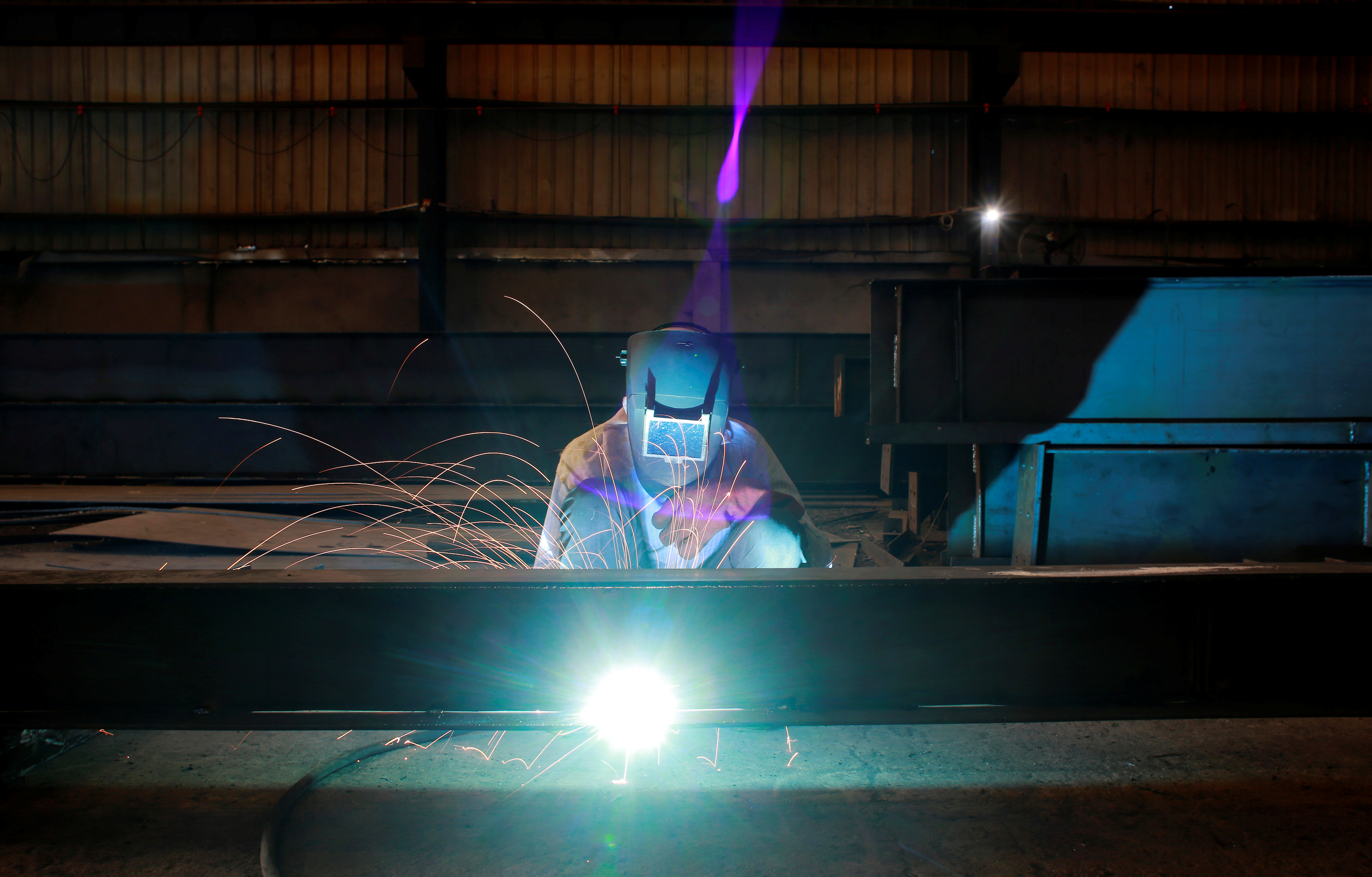 A labourer welds an iron pillar at a building material factory in an industrial area in Dasna, in the central Indian state of Uttar Pradesh, India, January 9, 2019. REUTERS/Adnan Abidi/File Photo
