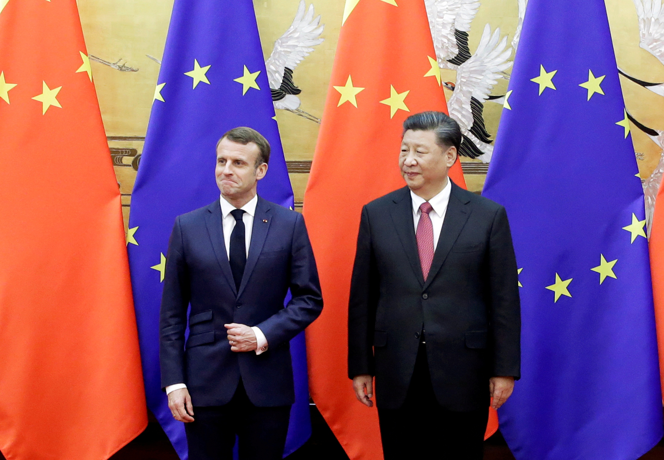 Chinese President Xi Jinping and French President Emmanuel Macron stand in front of Chinese and EU flags at a signing ceremony inside the Great Hall of the People in Beijing, China November 6, 2019.  REUTERS/Jason Lee/Pool/File Photo