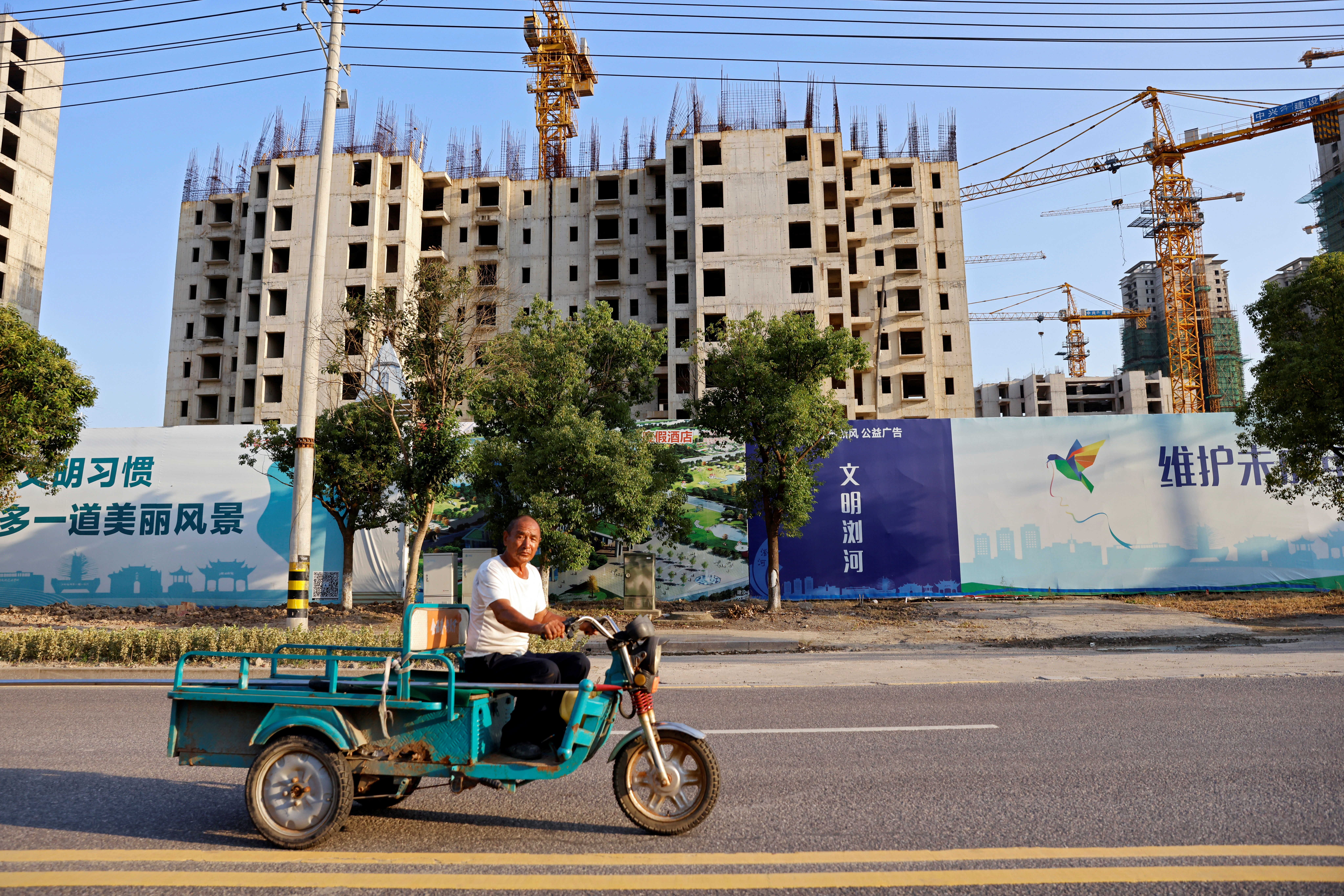 A man rides a vehicle past the construction site of Evergrande Cultural Tourism City, a project developed by China Evergrande Group, in Suzhou's Taicang, Jiangsu province, China September 23, 2021. REUTERS/Aly Song/File Photo