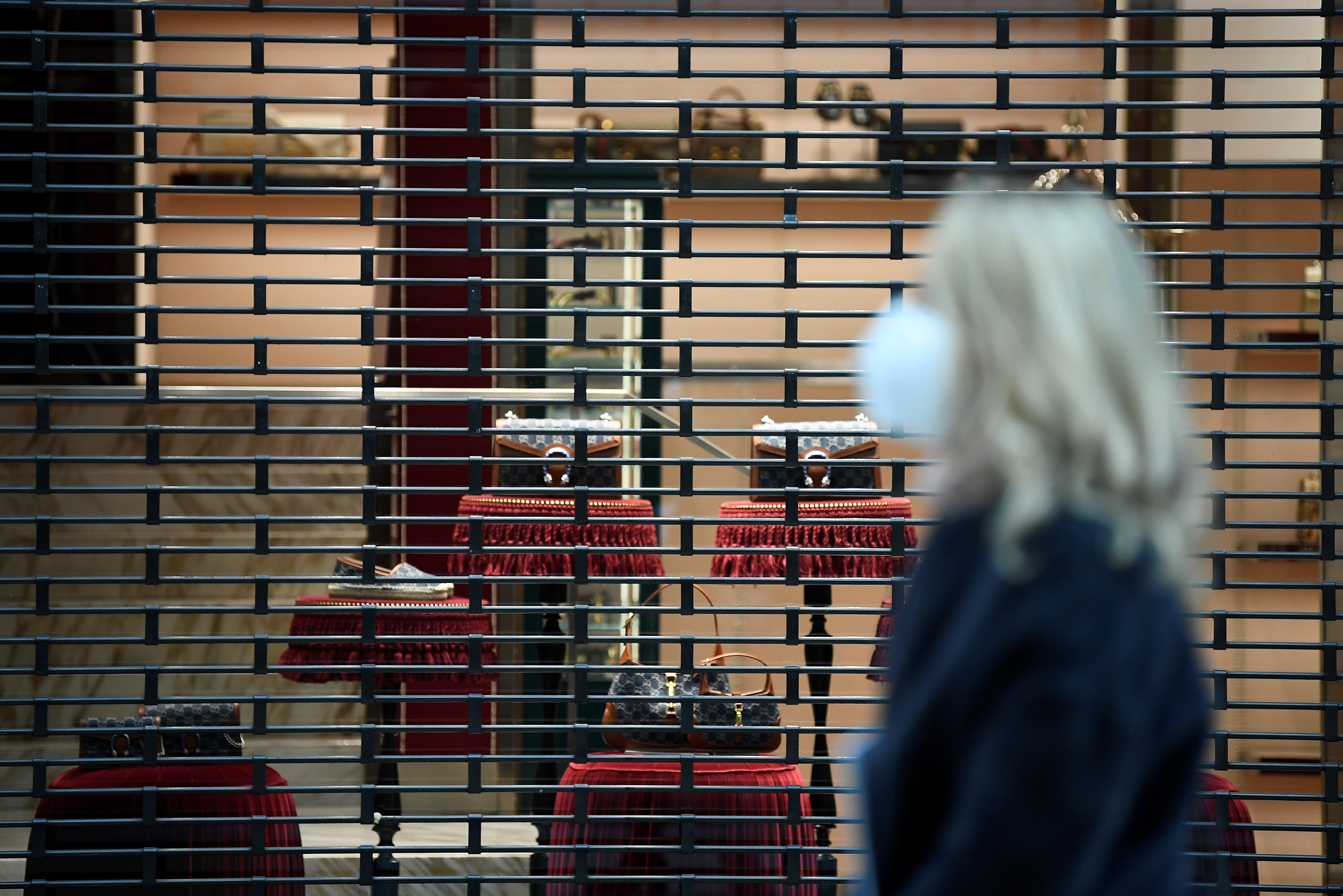 A woman wearing a protective face mask walks past a closed shop as the region of Lombardy becomes a 'red zone', going into lockdown as the country struggles to reduce the coronavirus disease (COVID-19) infections, in Milan, Italy, March 15, 2021. REUTERS/Flavio Lo Scalzo/File Photo