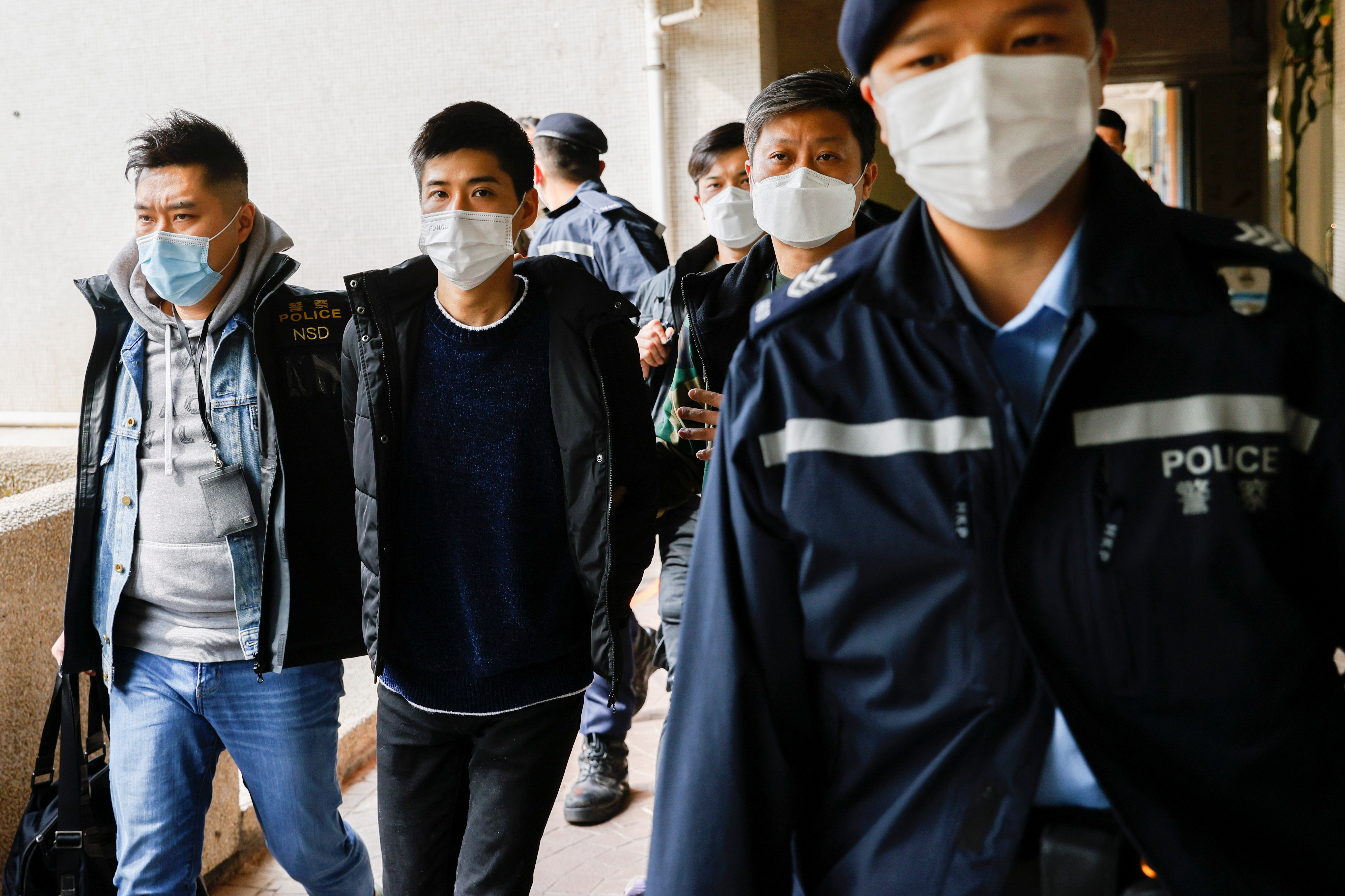 Pro-democracy activist Lester Shum is taken away by police officers as more than 50 Hong Kong activists are arrested under a security law in Hong Kong, China January 6, 2021. Picture taken January 6, 2021.   REUTERS/Stringer