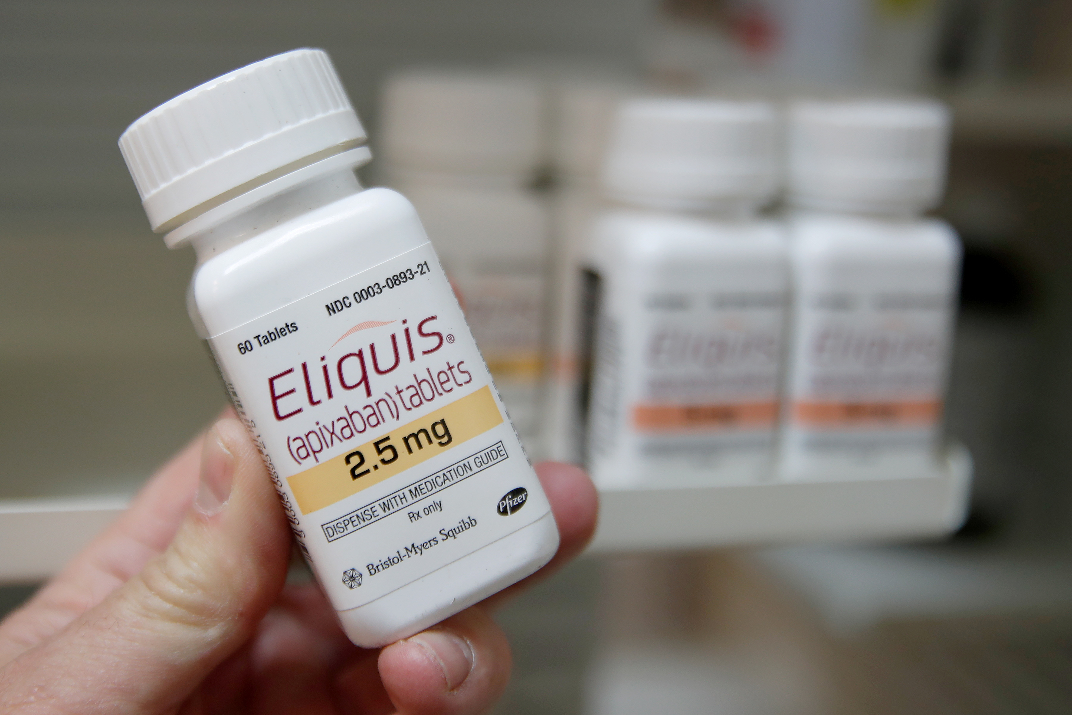 A pharmacist holds a bottle of the drug Eliquis,  sold by Bristol Myers Sqibb and Pfizer at a pharmacy in Provo, Utah, U.S. January 9, 2020.   REUTERS/George Frey