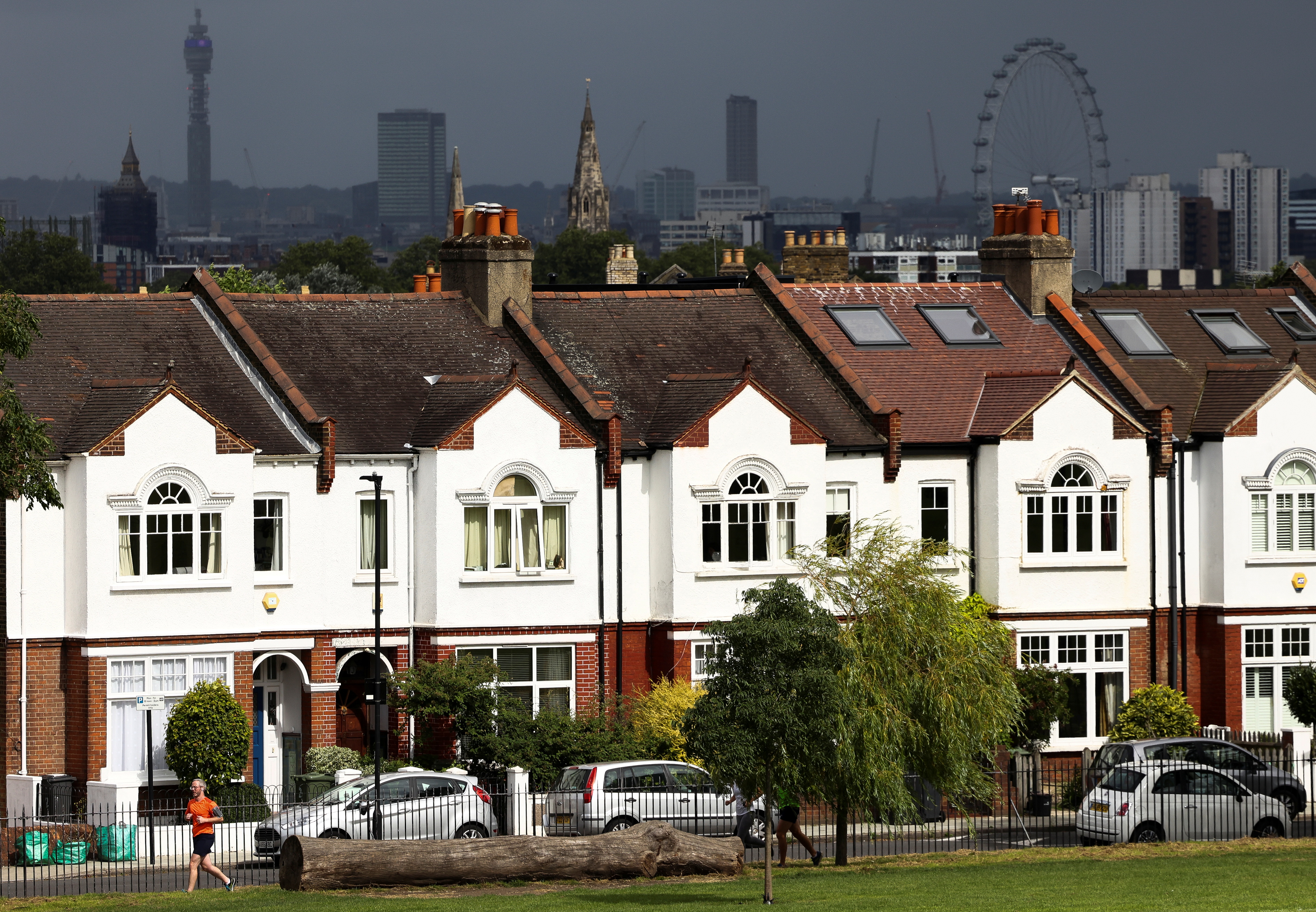 A person jogs past a row of residential housing in south London, Britain, August 6, 2021. REUTERS/Henry Nicholls