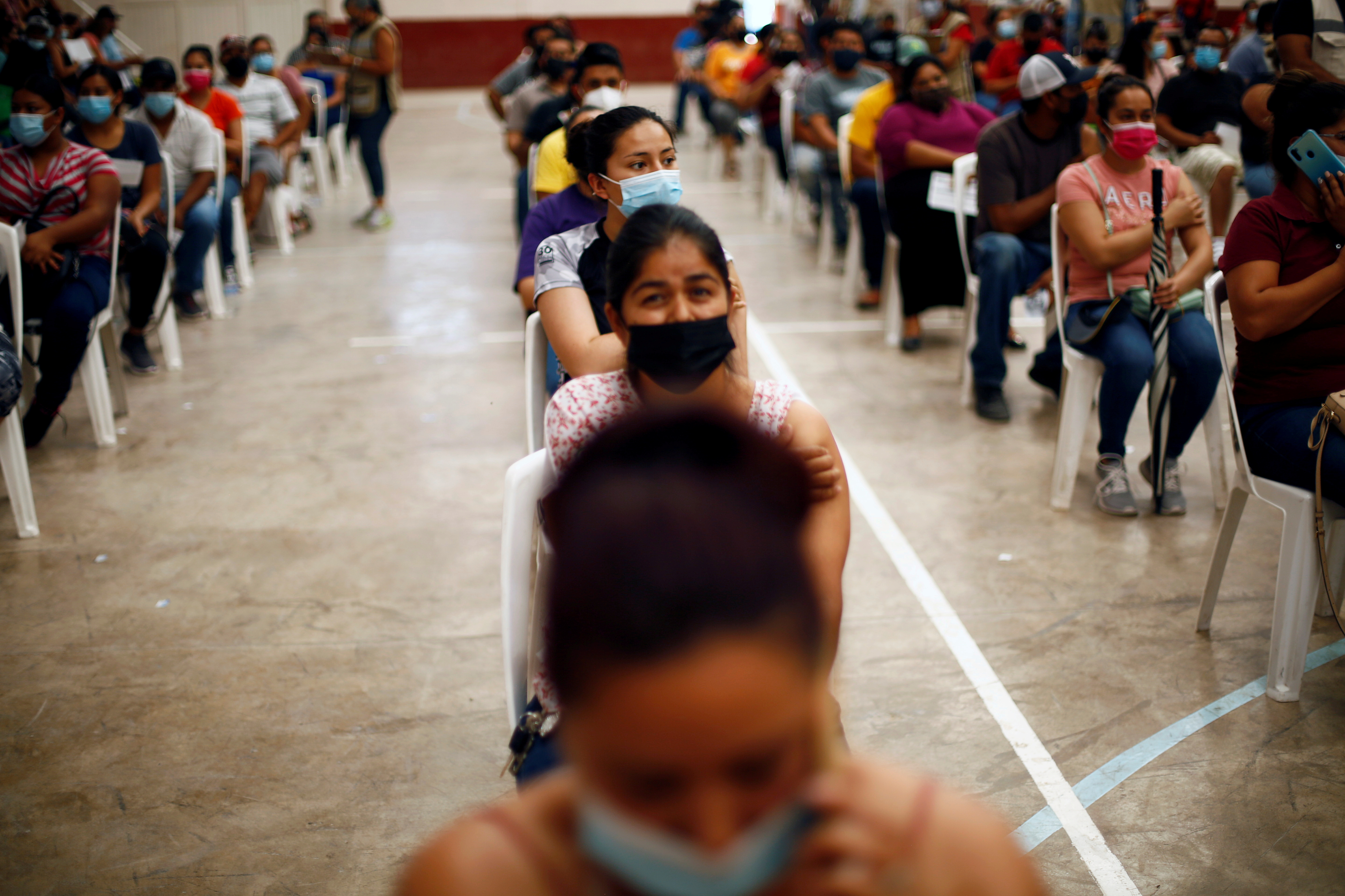 People wait after receiving a dose of the Pfizer-BioNTech coronavirus disease (COVID-19) vaccine during a mass vaccination program for people over 18 years of age at a gym in Praxedis G. Guerrero, Mexico July 10, 2021. REUTERS/Jose Luis Gonzalez/File Photo