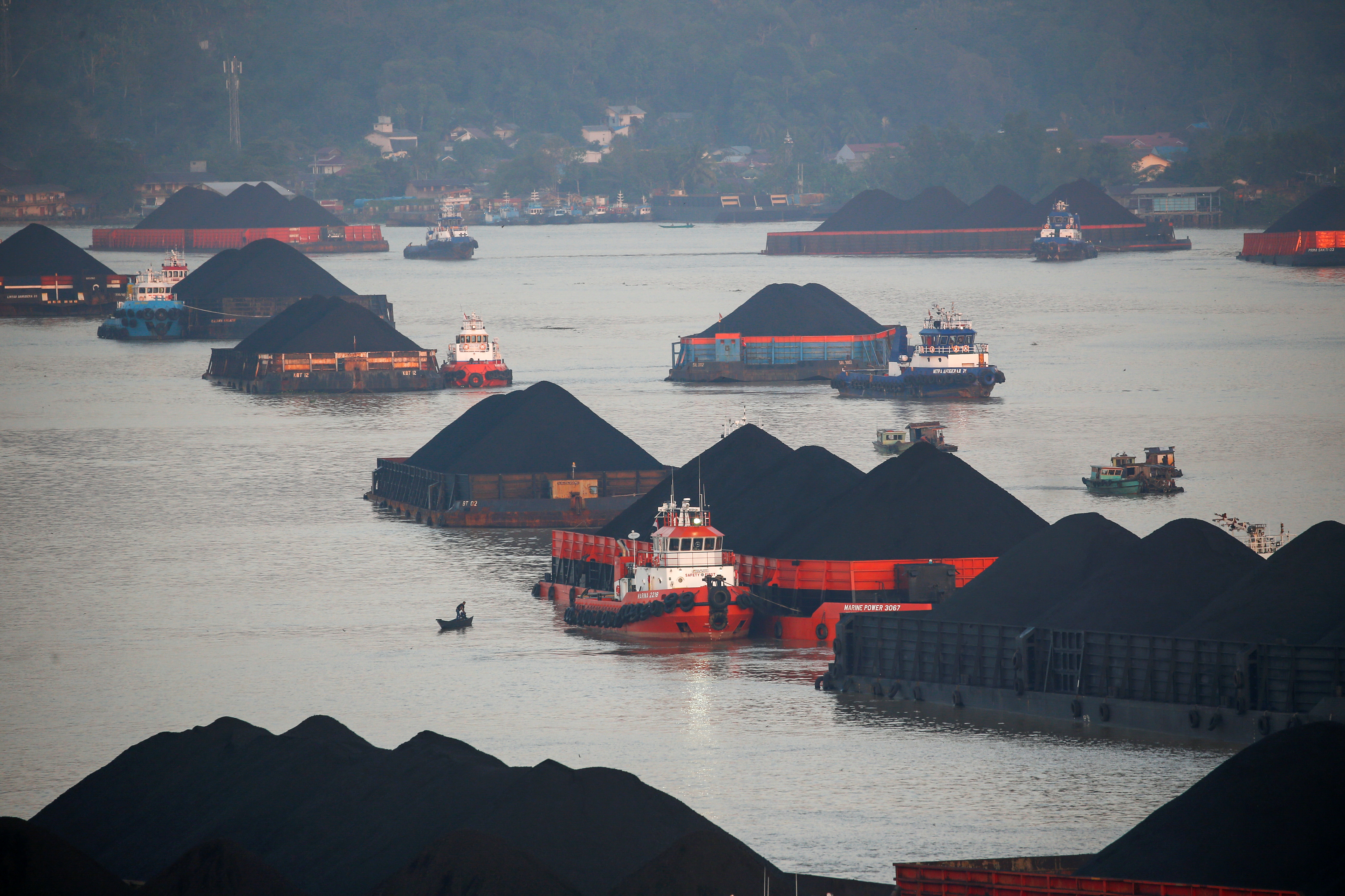 Coal barges are pictured as they queue to be pulled along Mahakam river in Samarinda, East Kalimantan province, Indonesia, August 31, 2019. Picture taken August 31, 2019. REUTERS/Willy Kurniawan