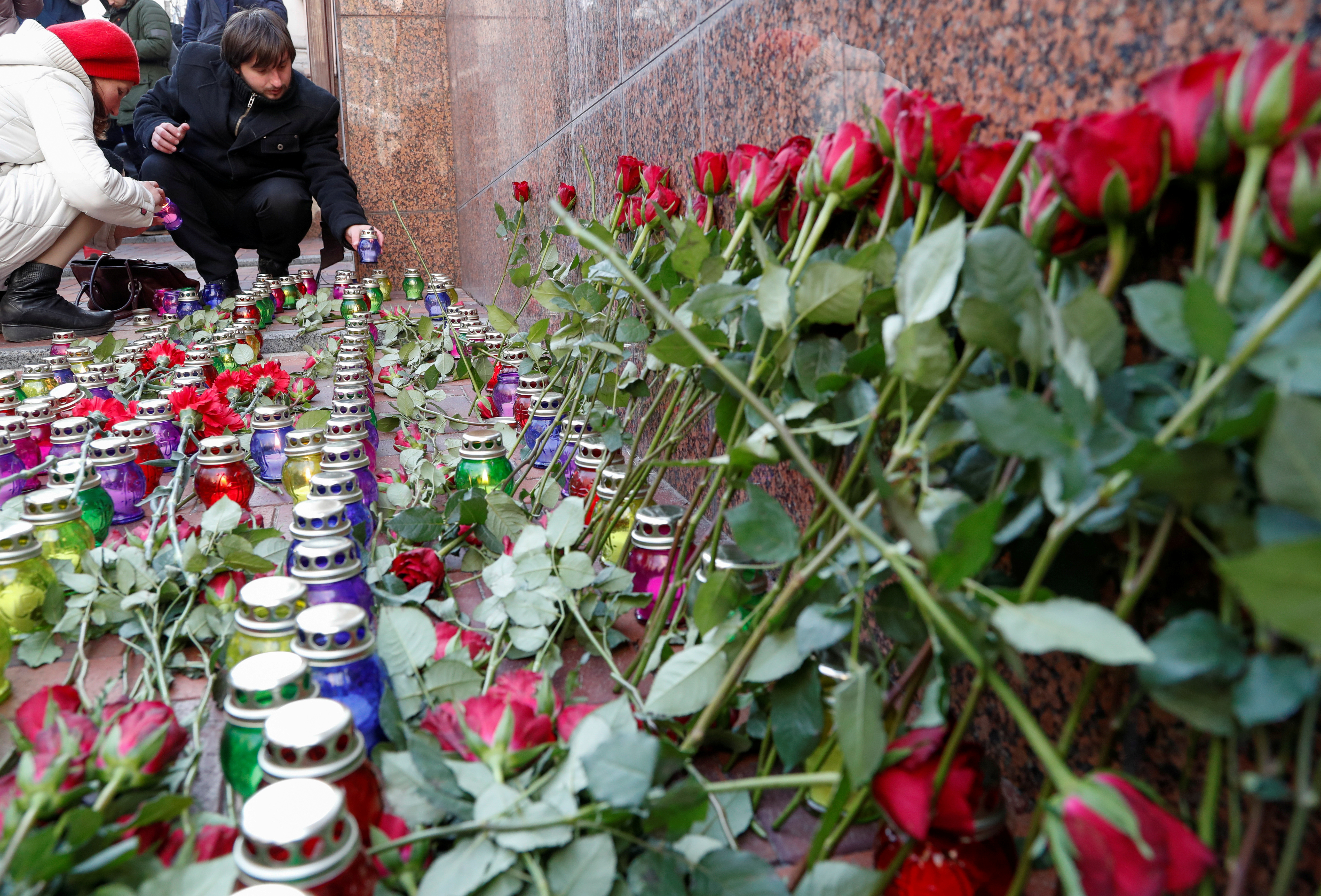 People place candles as they commemorate victims of the Ukraine International Airlines flight 752 plane disaster, in front of the Iranian embassy in Kiev, Ukraine February 17, 2020. REUTERS/Valentyn Ogirenko/File Photo