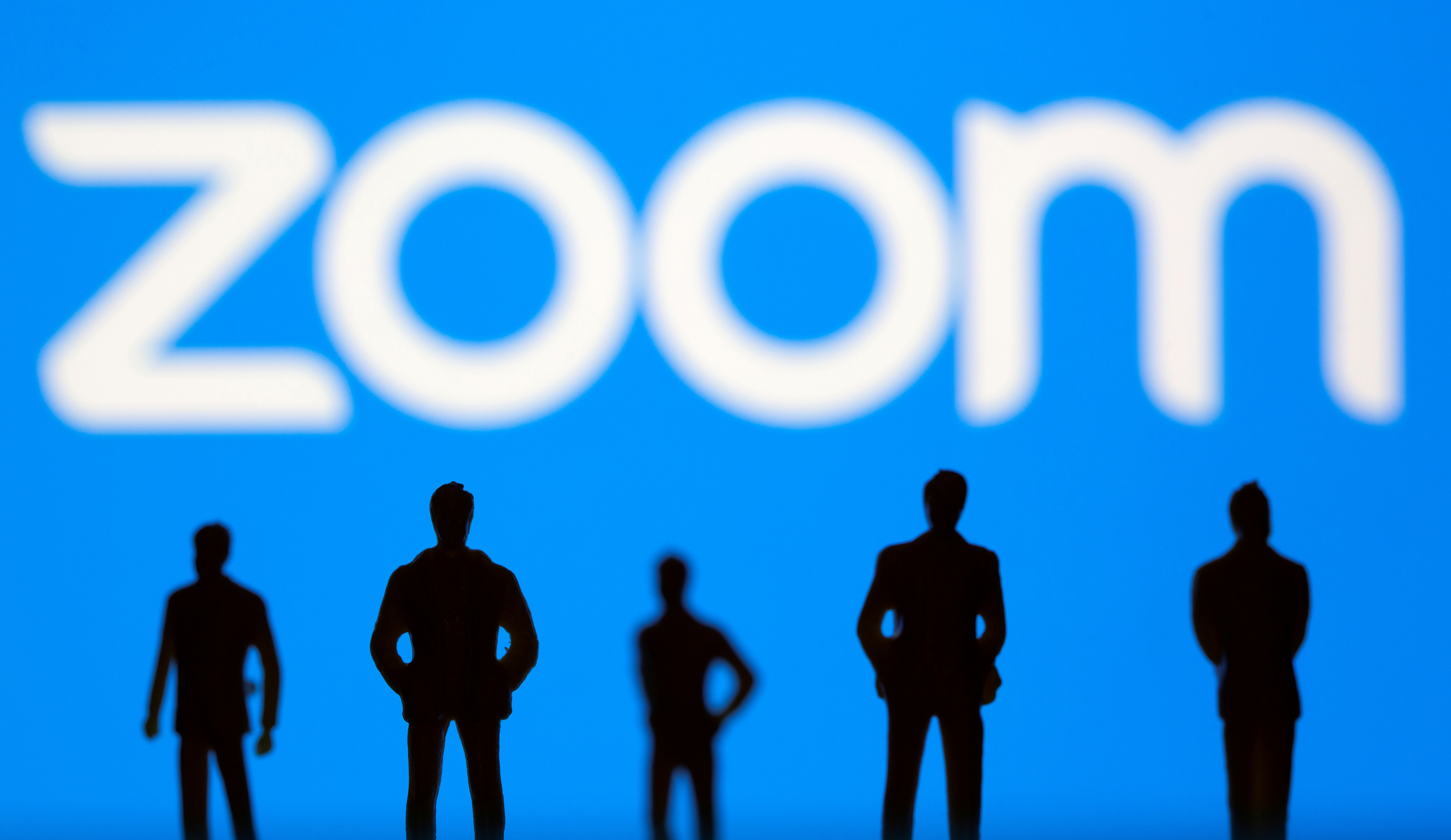 Small toy figures are seen in front of Zoom logo in this illustration picture taken March 15, 2021. REUTERS/Dado Ruvic/Illustration