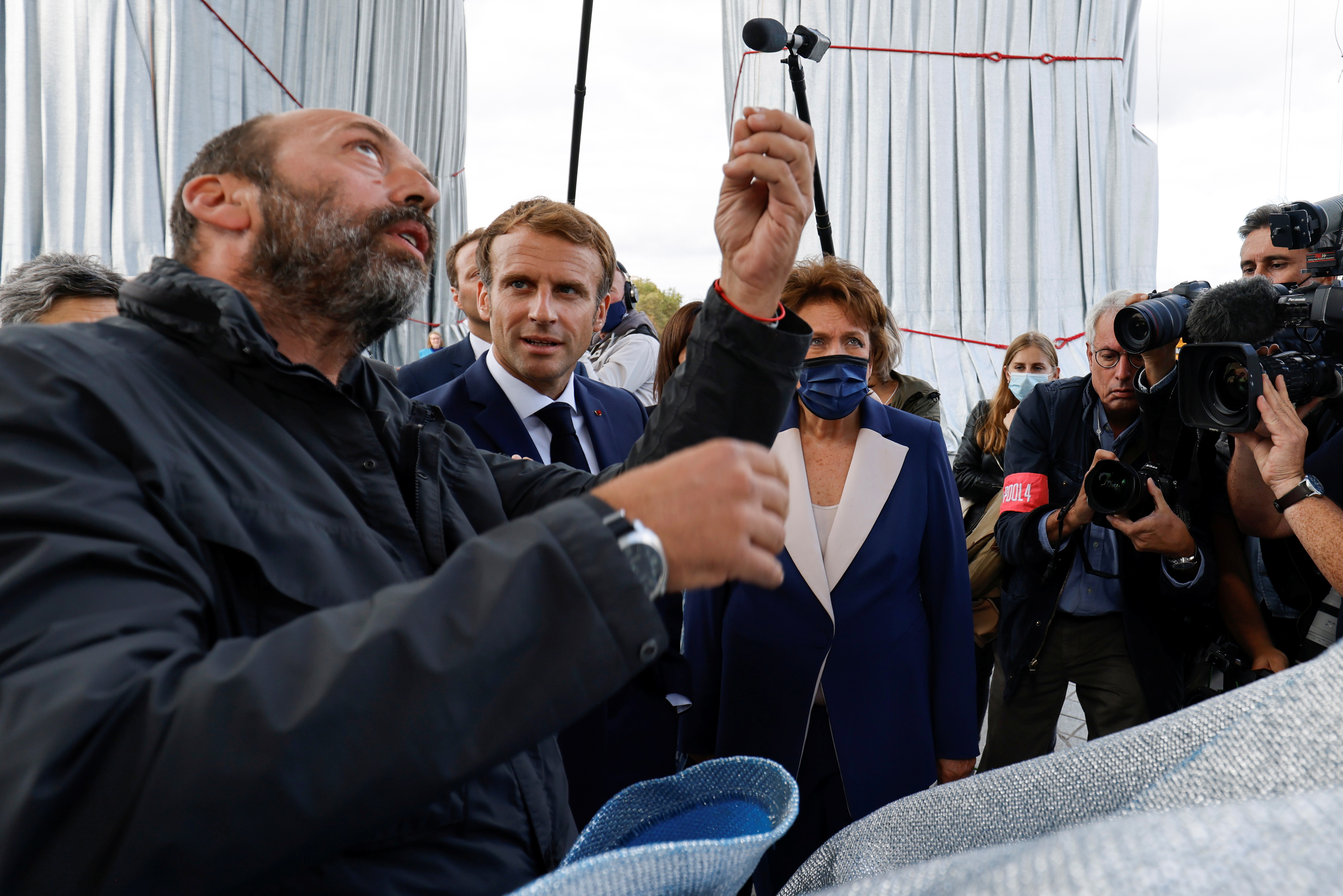 The nephew of late Bulgarian born artist Christo Vladimir Javacheff speaks to French President Emmanuel Macron and French Culture Minister Roselyne Bachelot during the inauguration of the wrapped Arc de Triomphe, designed by the late artist Christo, in Paris, France, September 16, 2021. Ludovic Marin/Pool via REUTERS