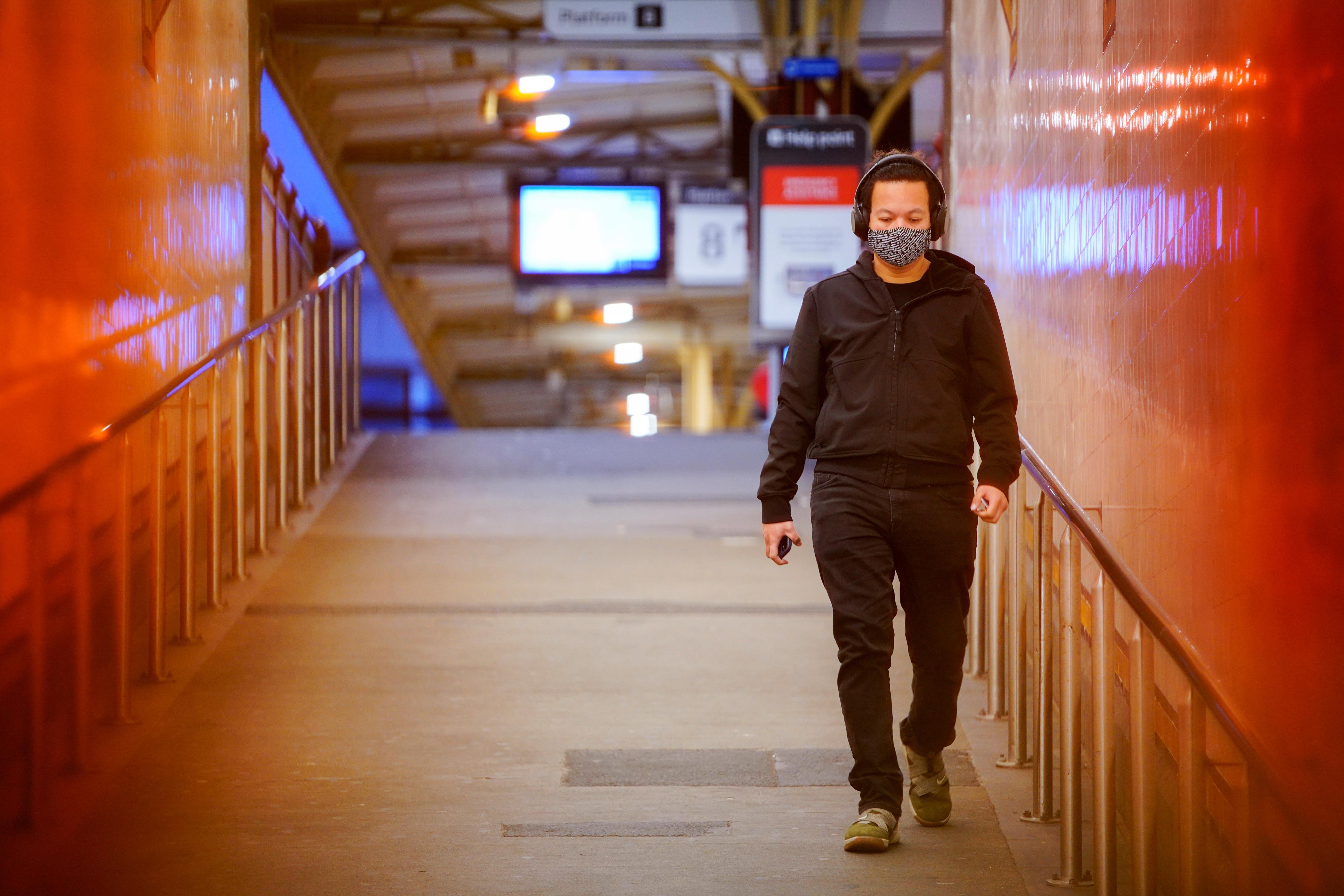 A lone passenger wearing a protective face mask walks from a deserted train platform at Flinders Street during morning commute hours on the first day of a lockdown as the state of Victoria looks to curb the spread of a coronavirus disease (COVID-19) outbreak in Melbourne, Australia, July 16, 2021. REUTERS/Sandra Sanders