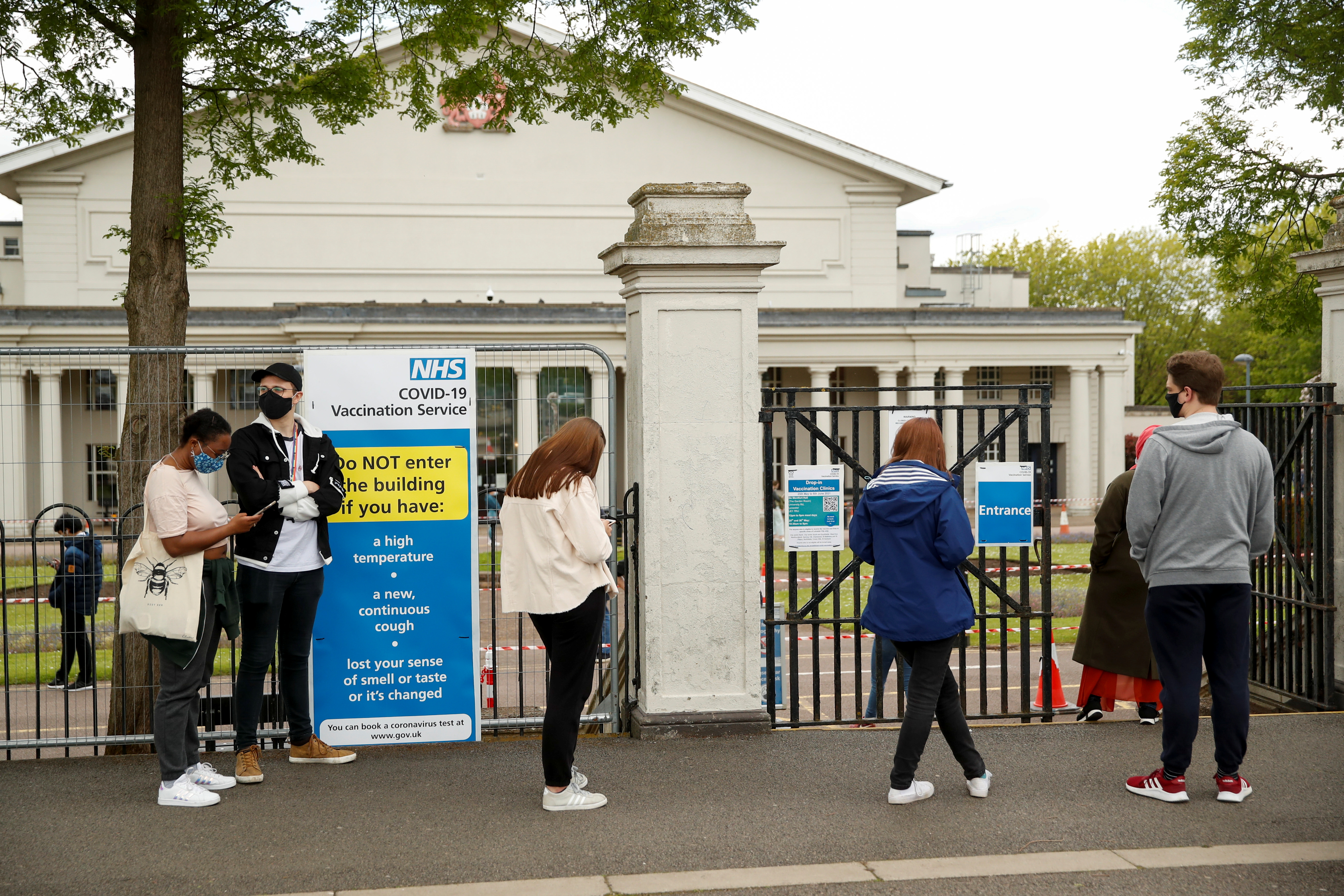 People wait in line in front of De Montfort Hall to receive the coronavirus disease (COVID-19) vaccine, in Leicester, Britain May 27, 2021. REUTERS/Andrew Boyers