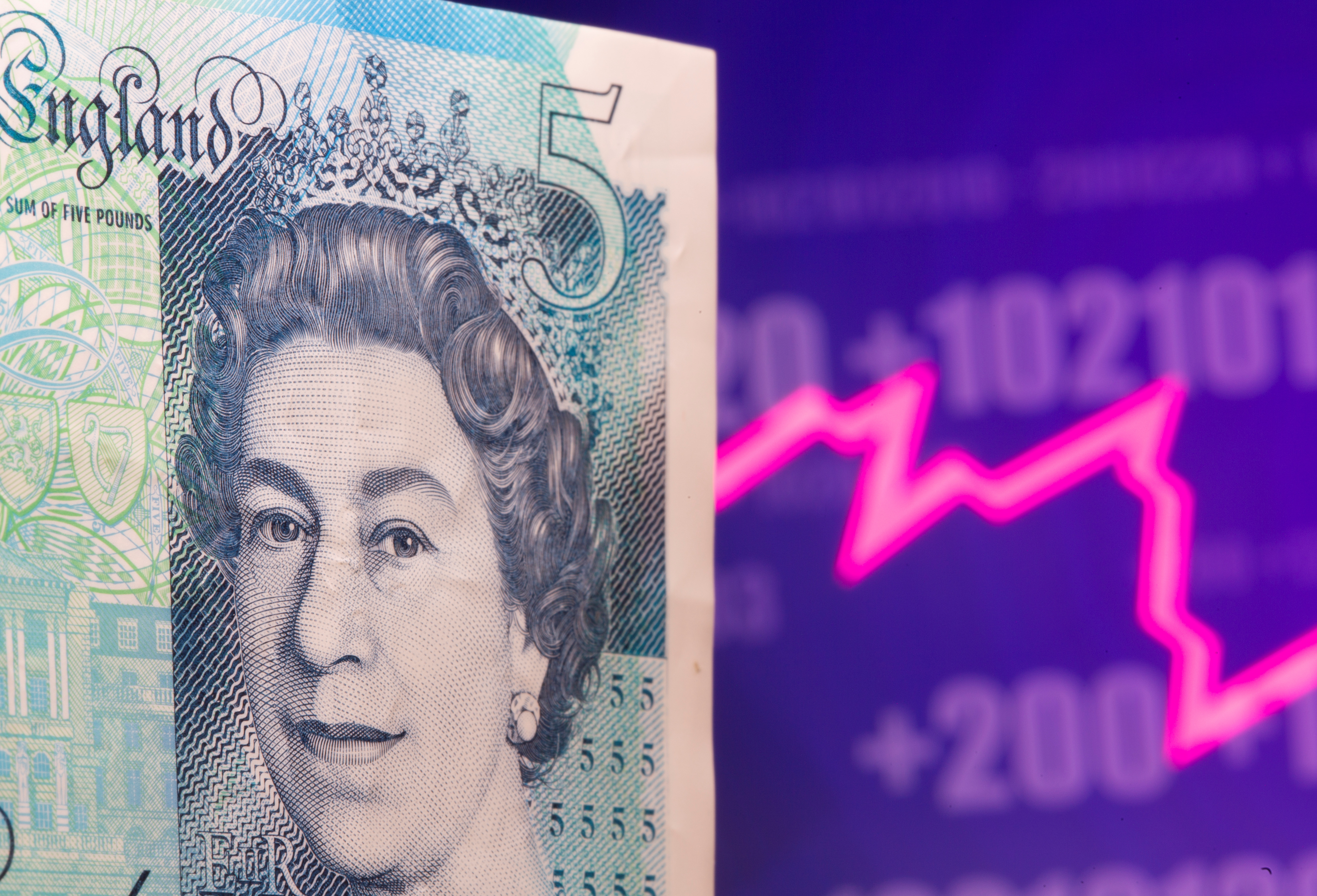 A British Pound banknote is seen in front of displayed stock graph in this illustration taken May 7, 2021. REUTERS/Dado Ruvic/Illustration/File photo