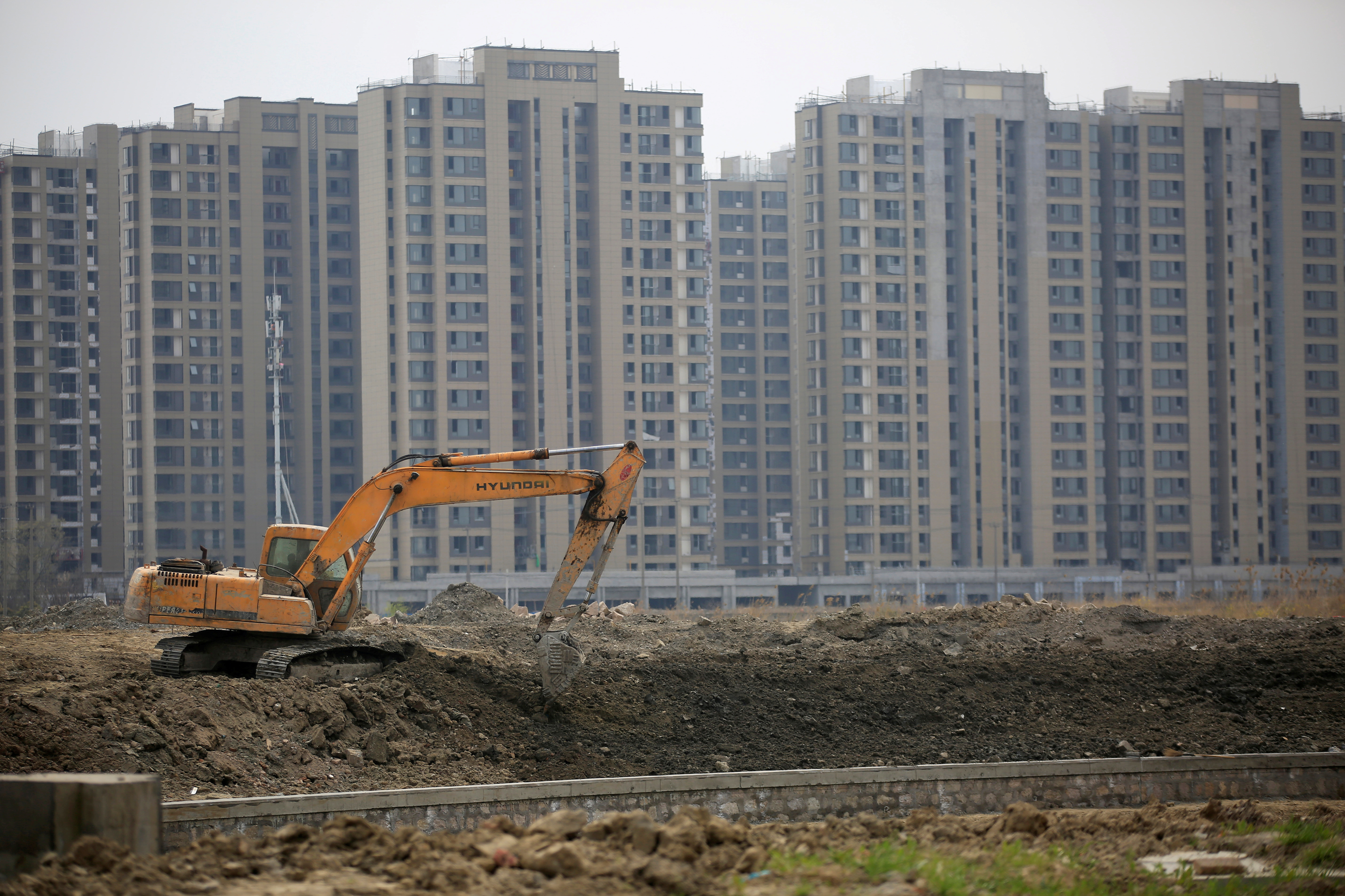 An excavator is seen at a construction site of new residential buildings in Shanghai, China, in this March 21, 2016 file photo. REUTERS/Aly Song/File Photo
