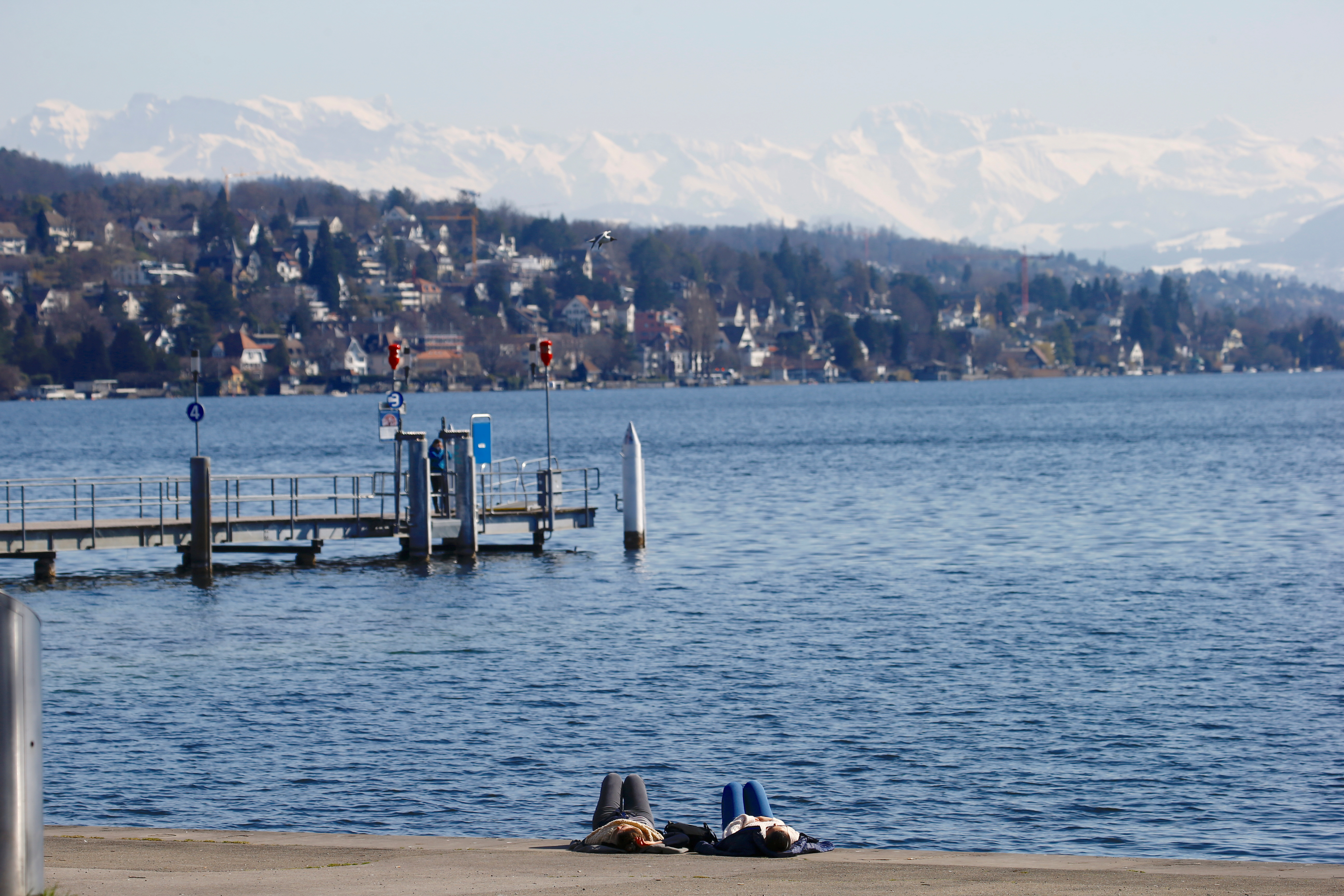 Women relax on the banks of Lake Zurich on a sunny spring day, as the spread of the coronavirus (COVID-19) continues, in Zurich, Switzerland March 23, 2021. REUTERS/Arnd Wiegmann/