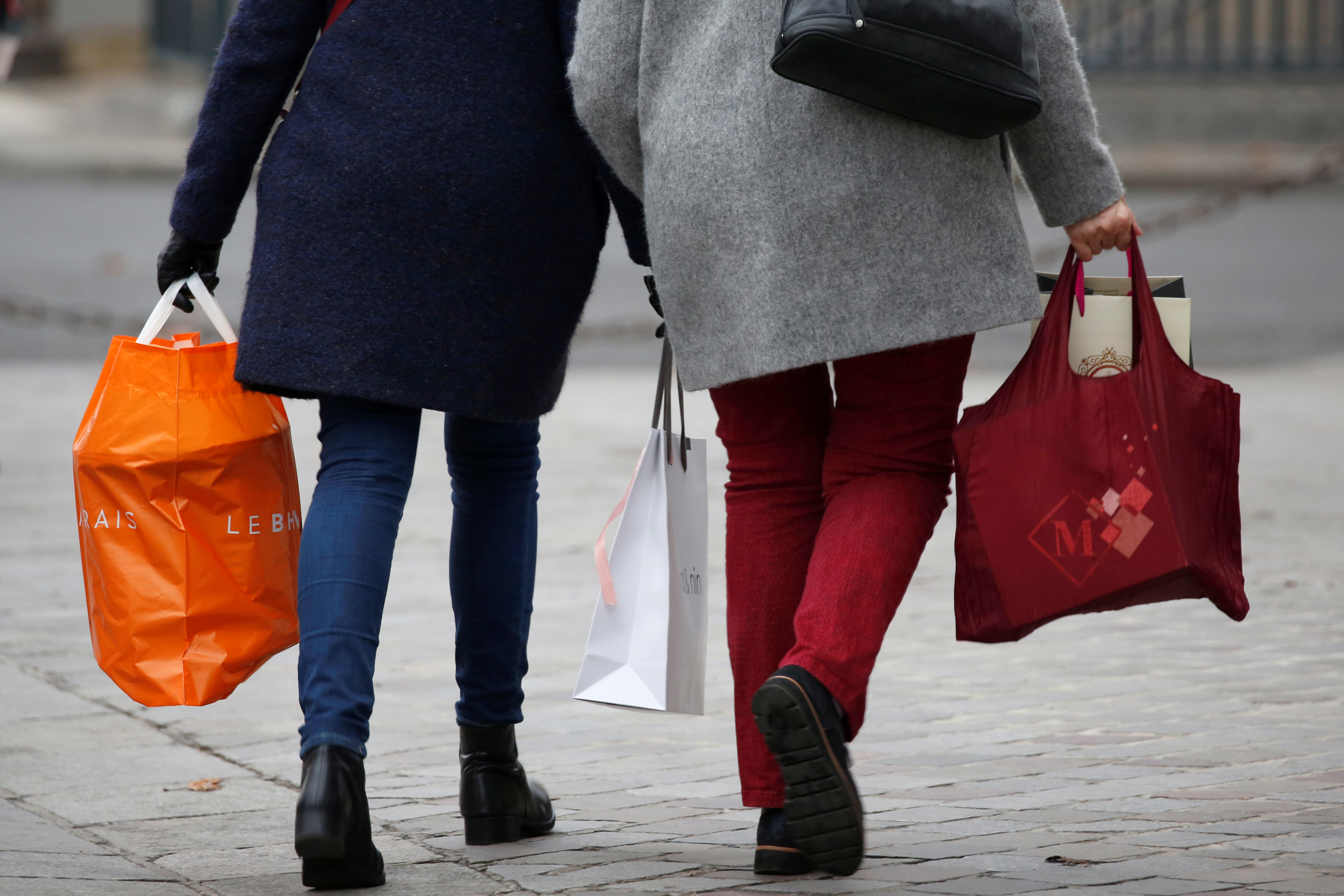 Shoppers walk with shopping bags as they take care of their last-minute Christmas holiday gift purchases outside department stores in Paris, France, December 23, 2016.  REUTERS/Charles Platiau