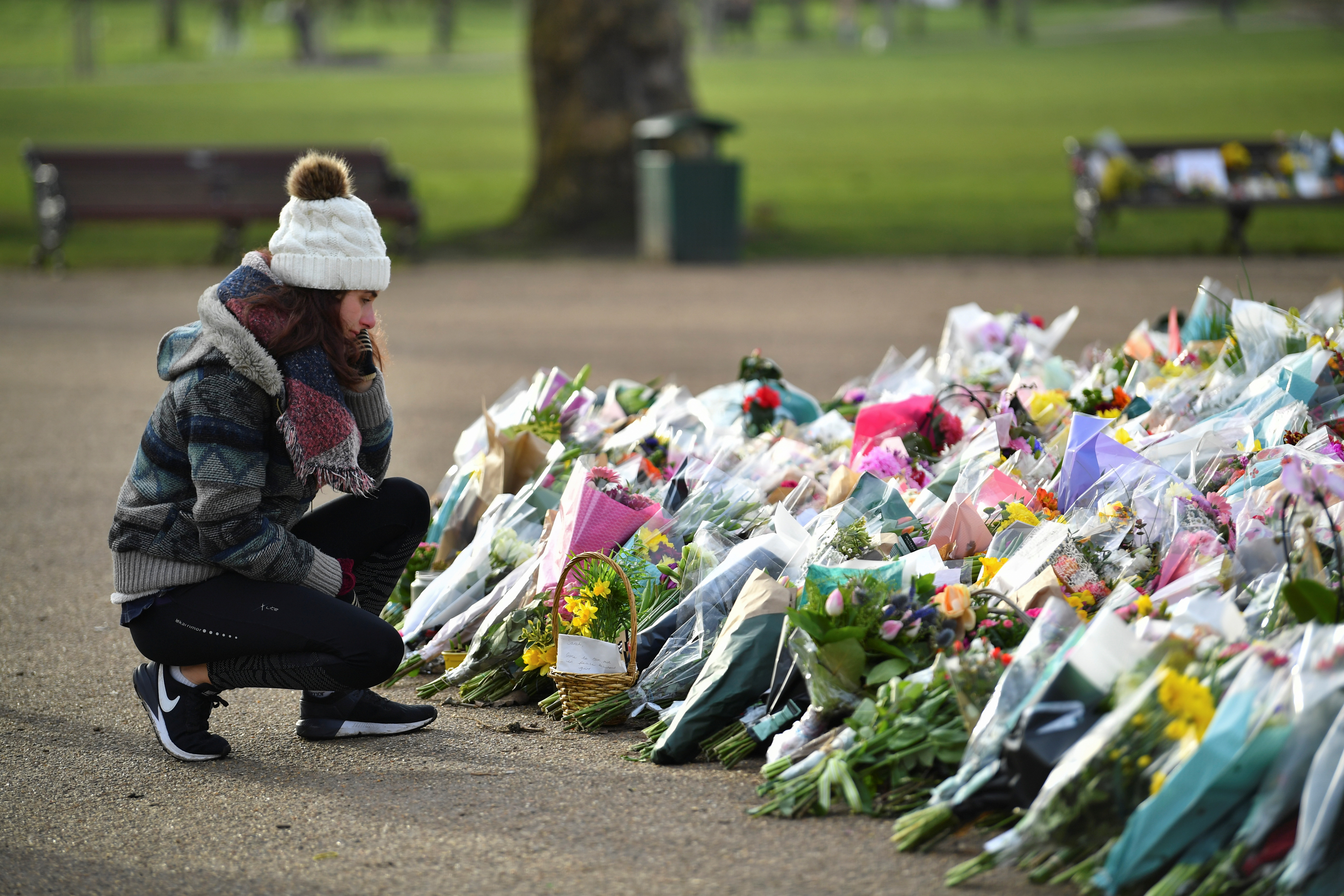 A woman reacts as she visits the memorial site at the Clapham Common Bandstand, following the kidnap and murder of Sarah Everard, in London, Britain, March 17, 2021. REUTERS/Dylan Martinez