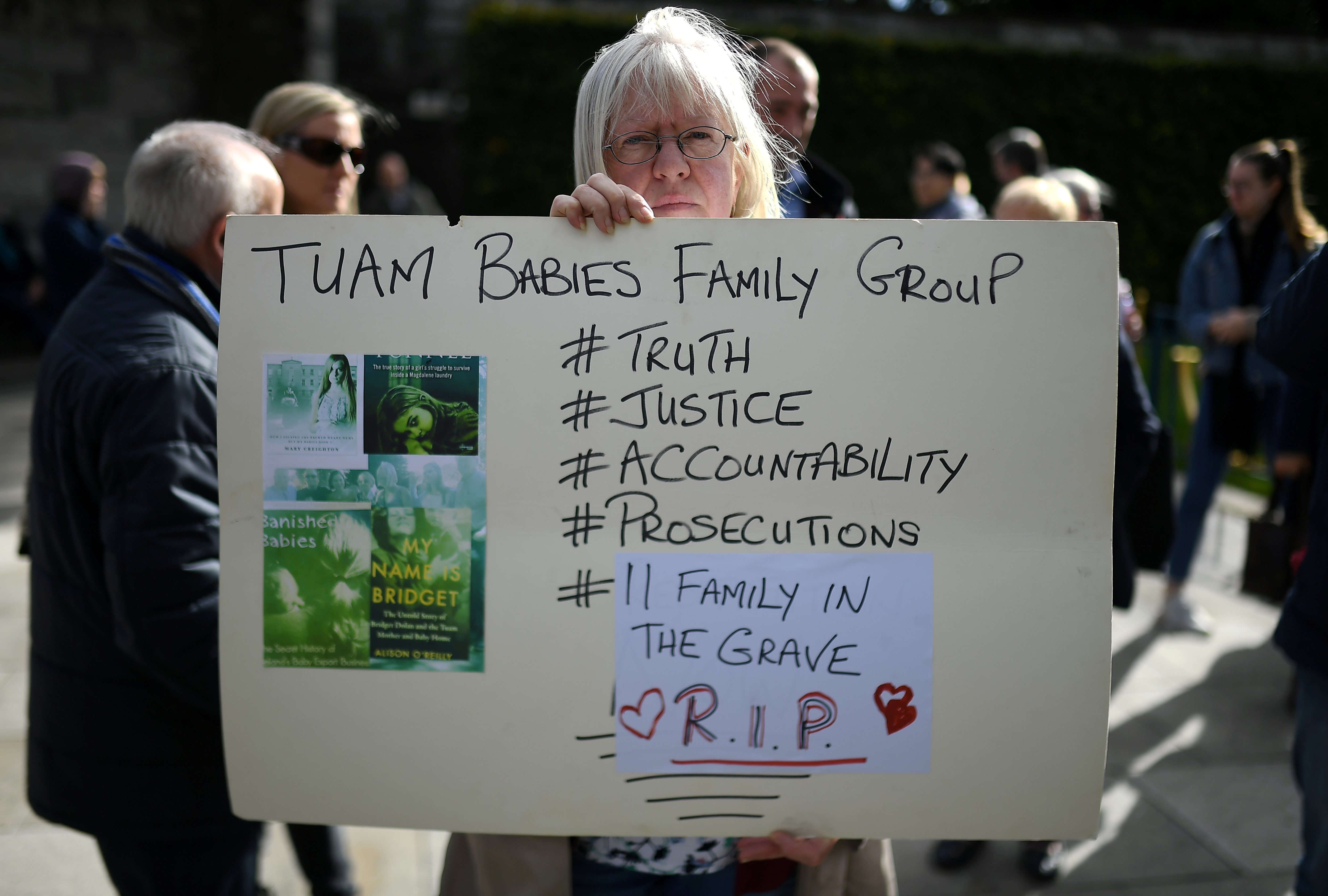 A woman holds a poster at a funeral procession in remembrance of the bodies of the infants discovered in a septic tank, in 2014, at the Tuam Mother and Baby Home, in Dublin, Ireland October 6, 2018. REUTERS/Clodagh Kilcoyne/File Photo