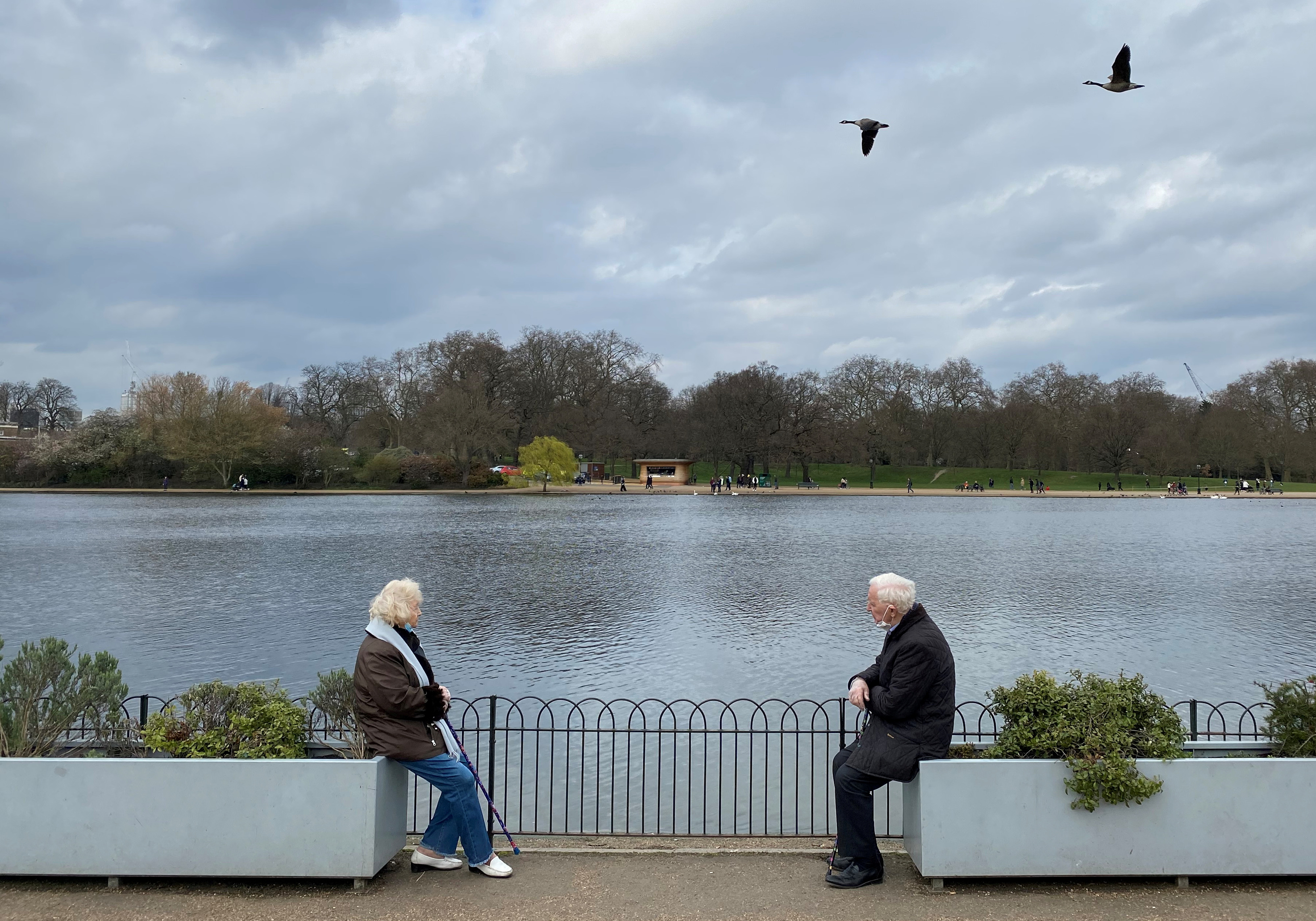 Two people are seen socially distancing as they chat together in Hyde Park, London, Britain, March 24, 2021. REUTERS/Toby Melville/File Photo