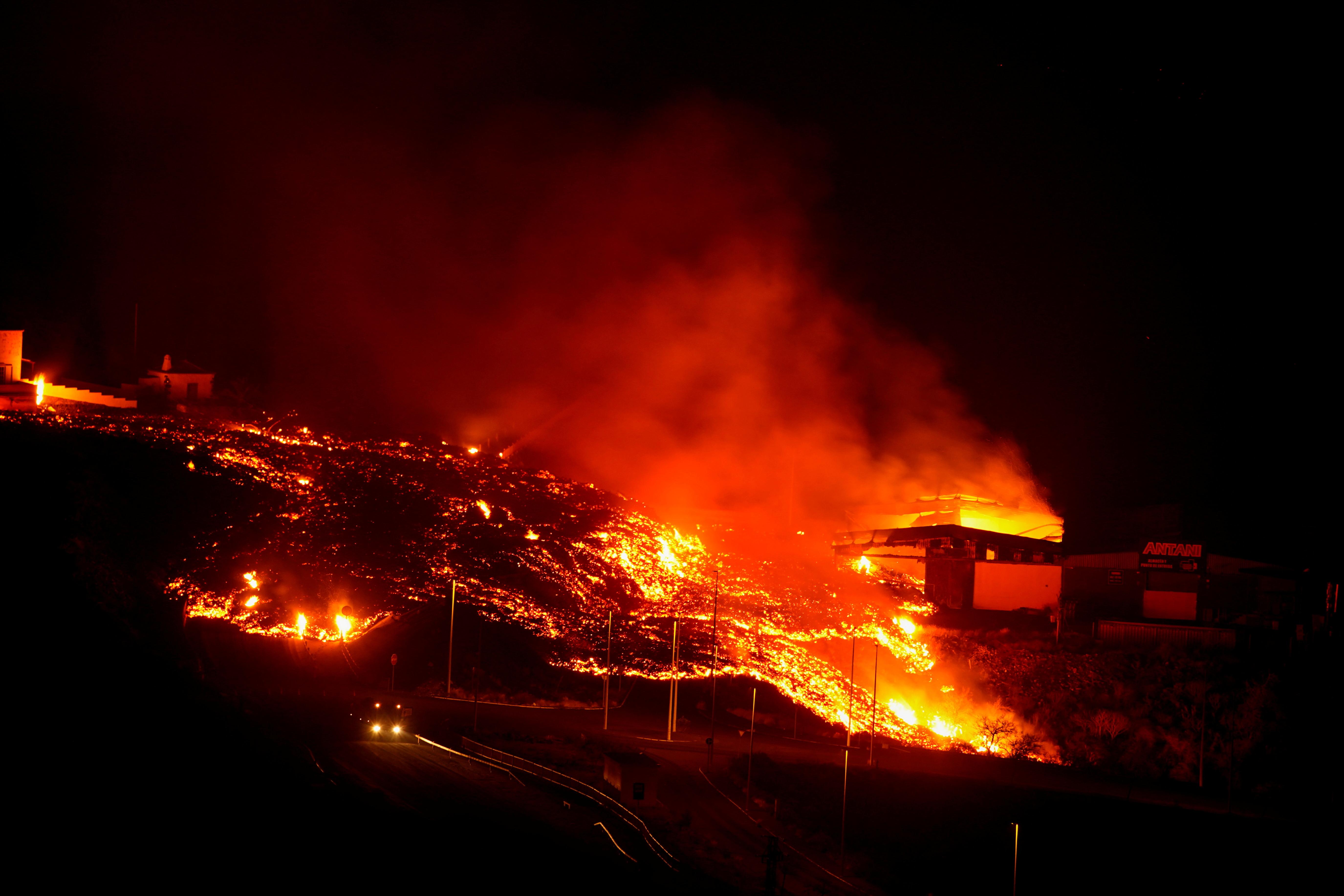 Lava burns buildings following the eruption of the Cumbre Vieja volcano, in Tacande, Spain, October 9, 2021. REUTERS/Juan Medina