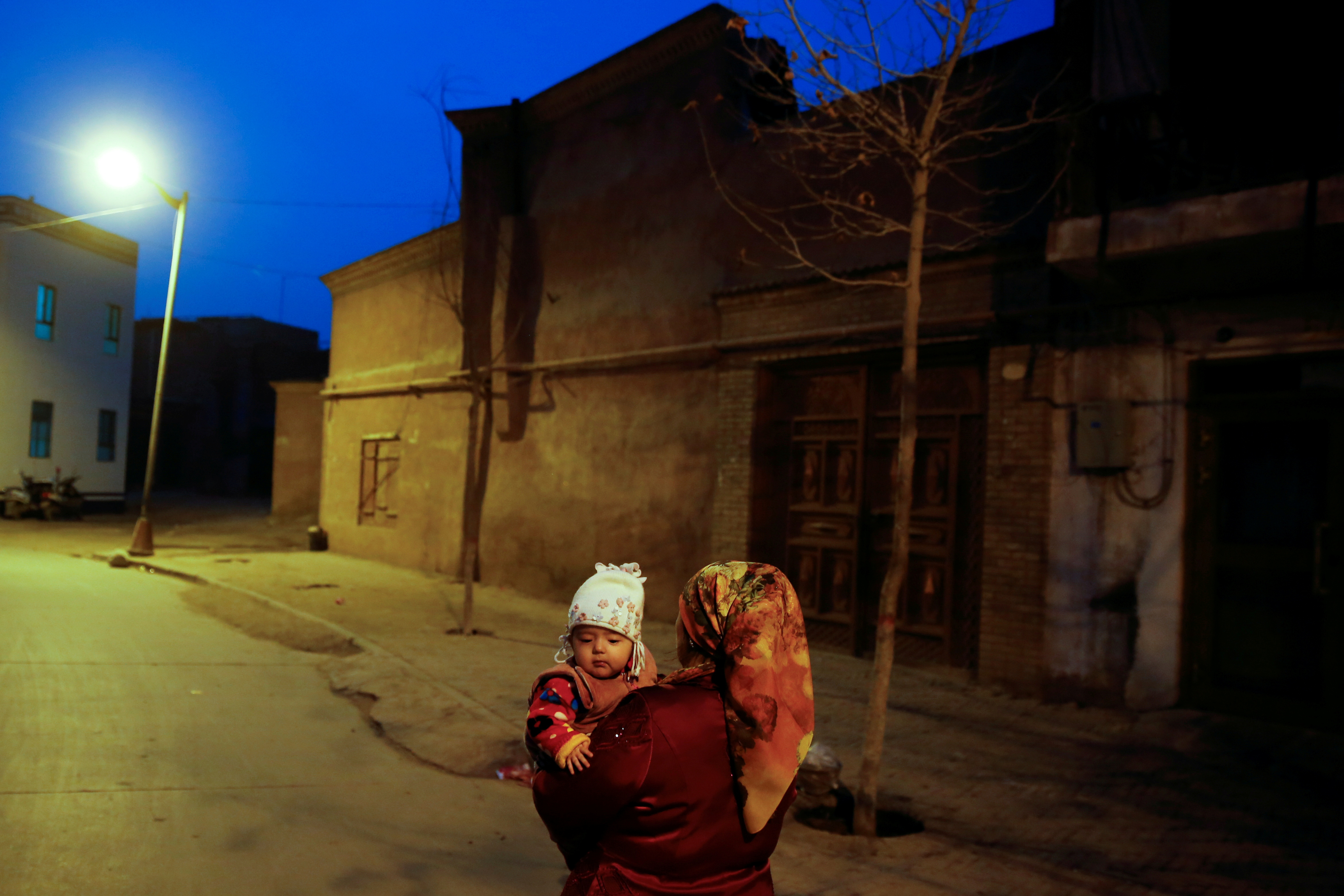 A woman carries a child at night in the old town of Kashgar, Xinjiang Uighur Autonomous Region, China, March 23, 2017.  REUTERS/Thomas Peter/File Photo