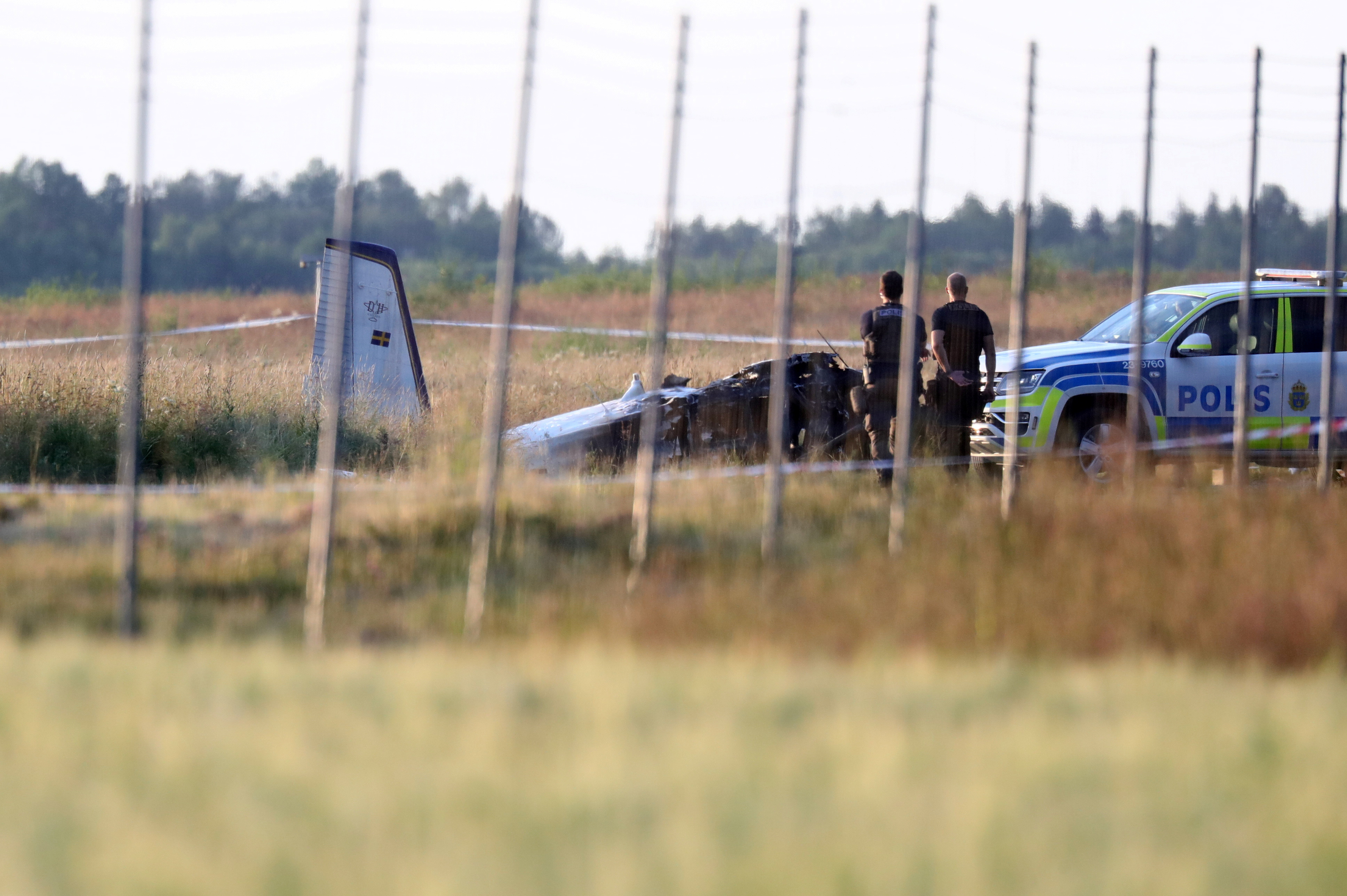 Police officers observe a small aircraft that crashed at Orebro Airport, Orebro, Sweden,  July 8 2021.  TT News Agency/Jeppe Gustafsson via REUTERS