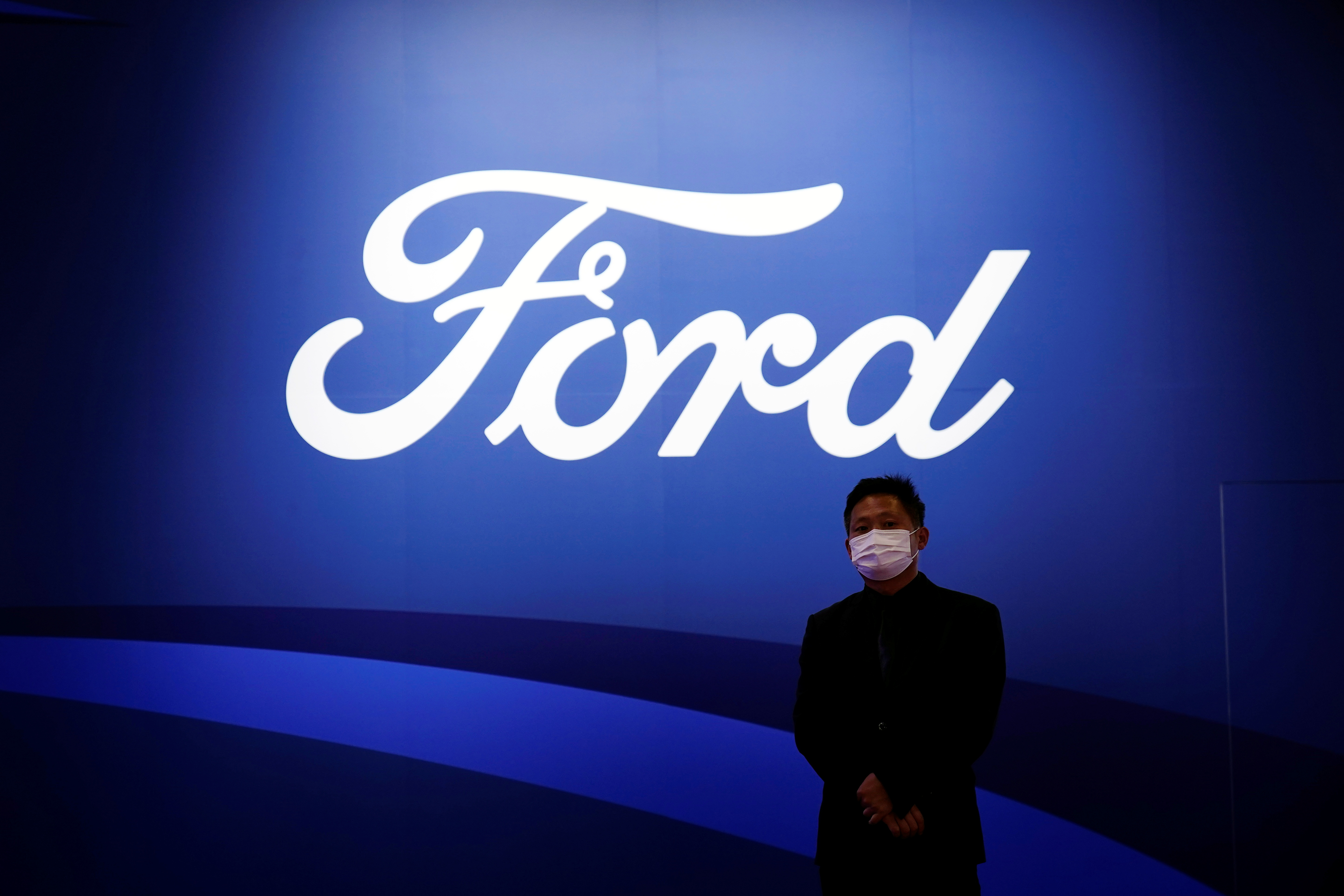 A man stands near the Ford logo during a media day for the Auto Shanghai show in Shanghai, China April 19, 2021. REUTERS/Aly Song/Files
