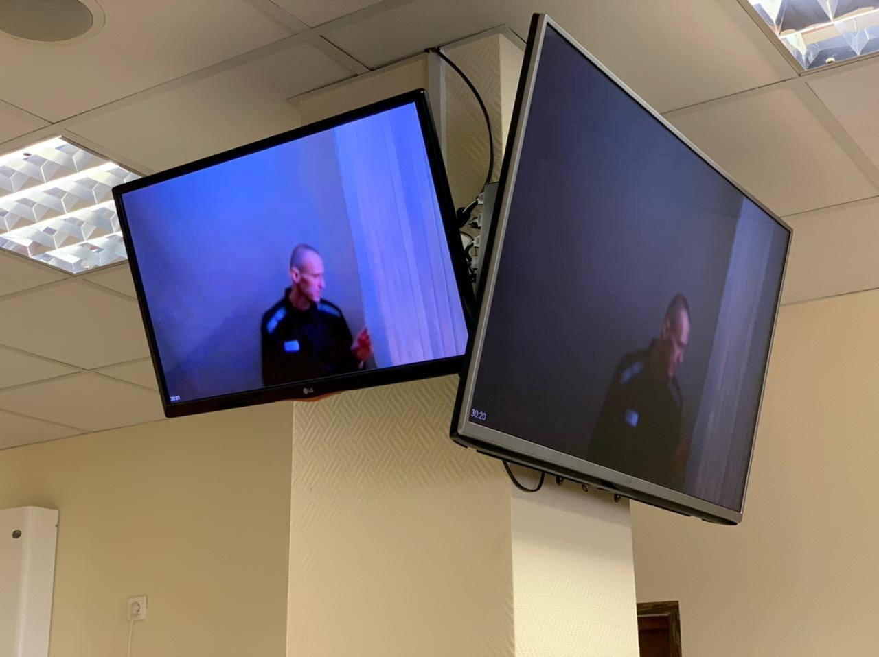 Krievijas opozīcijas līderis Aleksejs Navaļnijs pirms sēdes tiek rādīts ekrānos, izmantojot video saiti, lai izskatītu apelāciju par agrāku tiesas lēmumu, kas atzina viņu par vainīgu Krievijas Otrā pasaules kara veterāna nomelnošanā Maskavā, Krievijā, 29. gada 2021. aprīlī. Babuškinska preses dienests Maskavas apgabaltiesa / izdales materiāls, izmantojot REUTERS