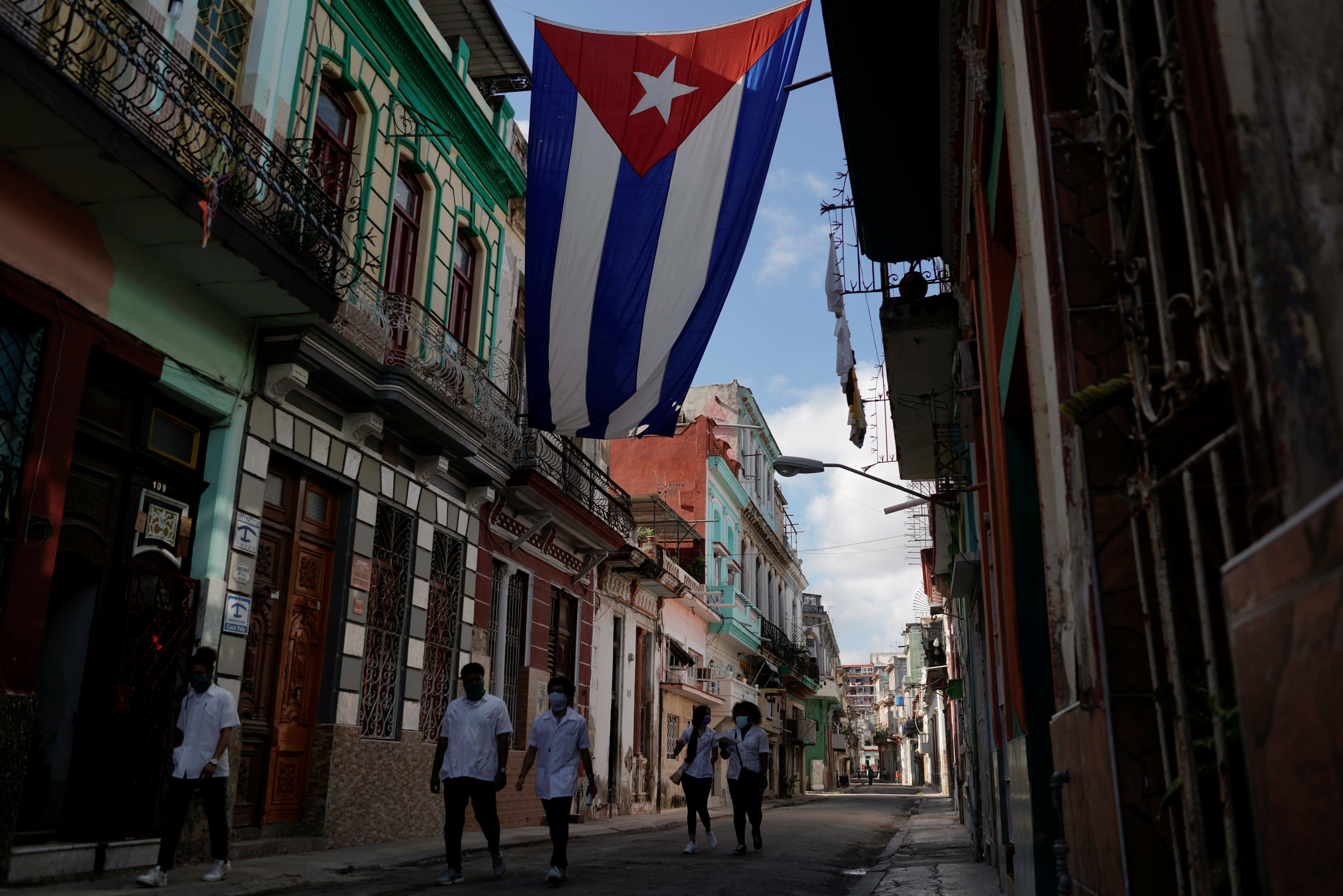 Medical students walk past a Cuban flag as they check door-to-door for people with symptoms amid concerns about the spread of the coronavirus disease (COVID-19), in downtown Havana, Cuba, May 12, 2020. REUTERS/Alexandre Meneghini