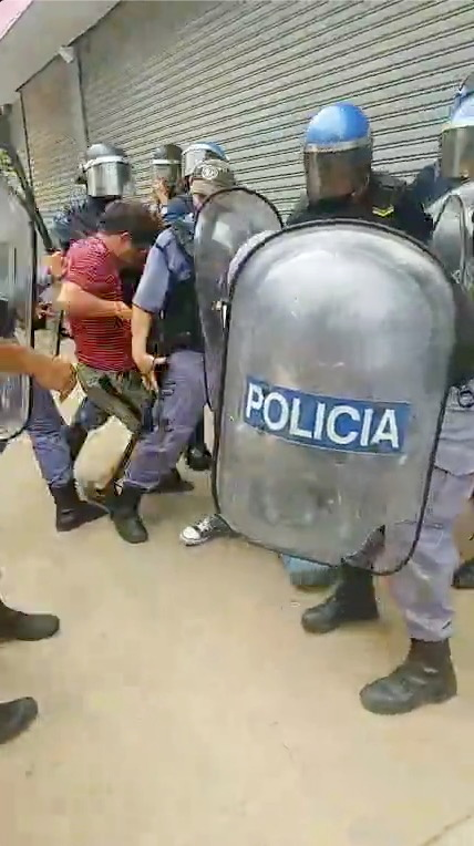 Riot police scuffle with a man protest tightening restrictions amid a spike in COVID-19 infections, in Formosa, Argentina in this still frame obtained from social media video dated March 5, 2021. INSTAGRAM @JOVENESXLALIBERTAD /via REUTERS