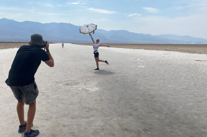 43-year-old Lana, a tourist from North Carolina poses for a picture holding an umbrella at Badwater Basin, the lowest point of North America below sea level in Death Valley, California, U.S. June 16, 2021. Picture taken June 16, 2021.  REUTERS/Norma Galeana