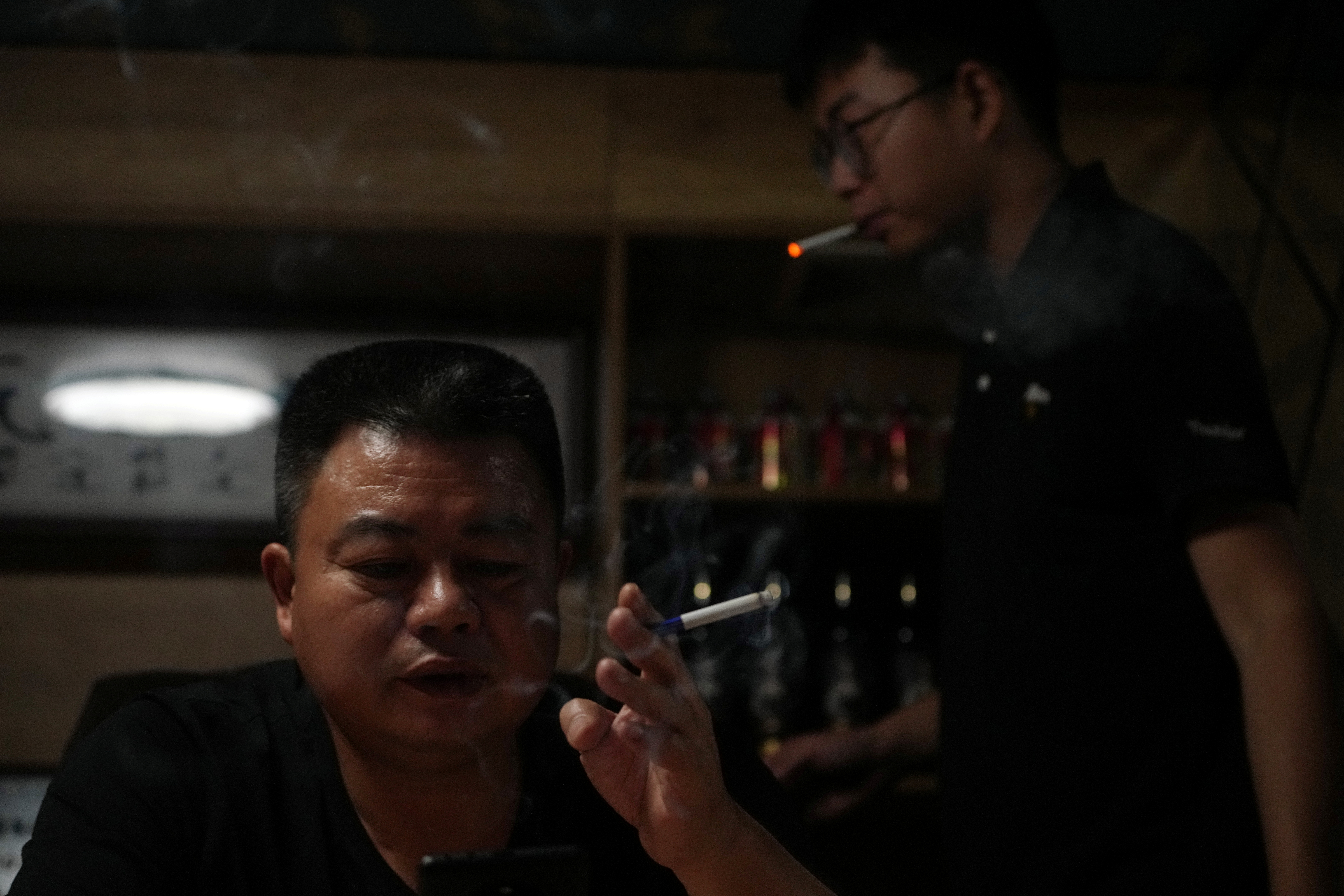 Guo Hui, whose cleaning business is owed money by China Evergrande Group, smokes a cigarette at his office in Guangzhou, Guangdong province, China September 26, 2021. Picture taken September 26, 2021. REUTERS/Aly Song